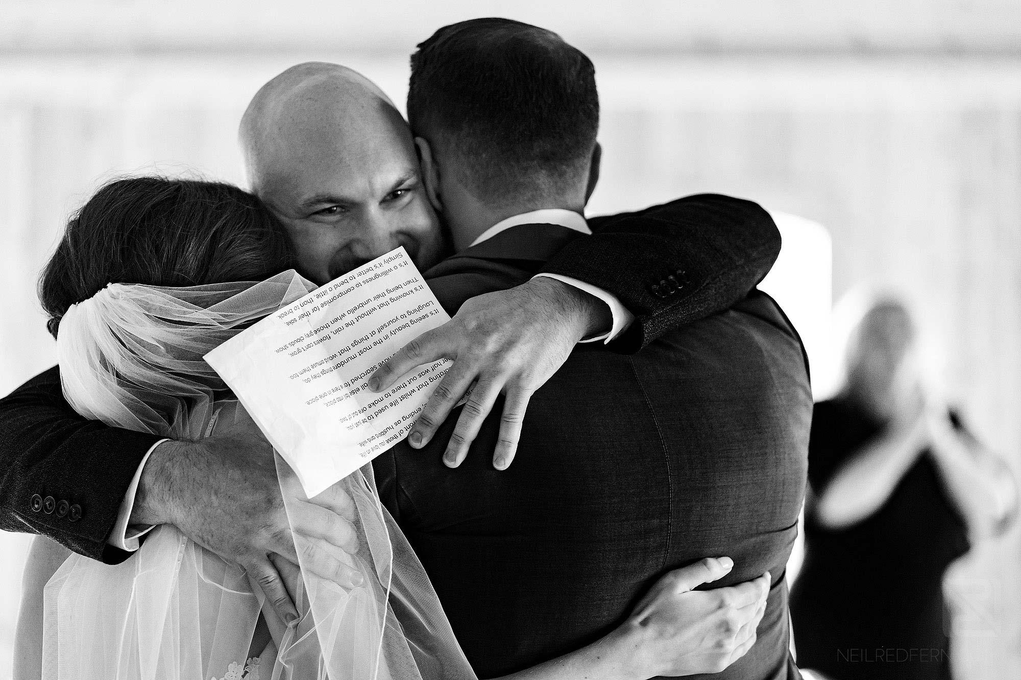 friend hugging newlyweds during wedding serivce