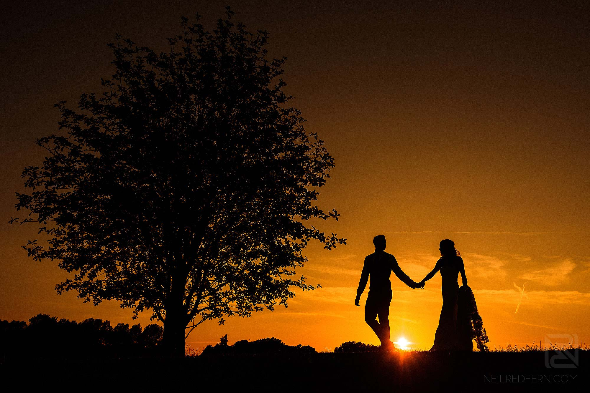 silhouette photograph of bride and groom at sunset