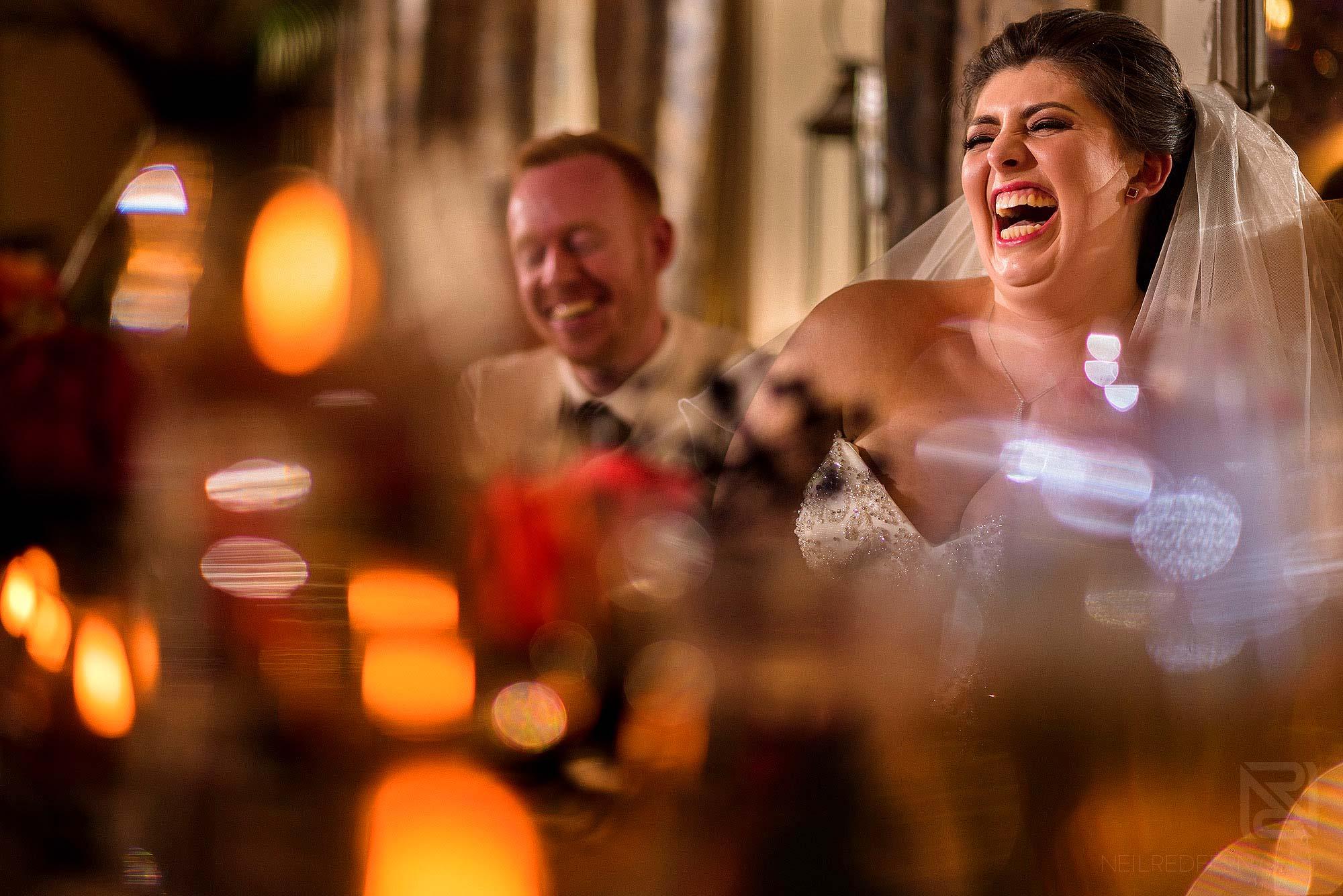 bride laughing during best man's wedding speech