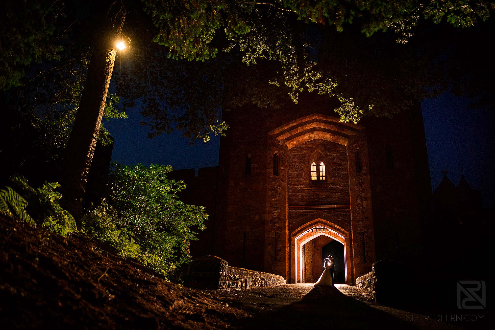 night time photograph of bride and groom outside Peckforton Castle in Cheshire