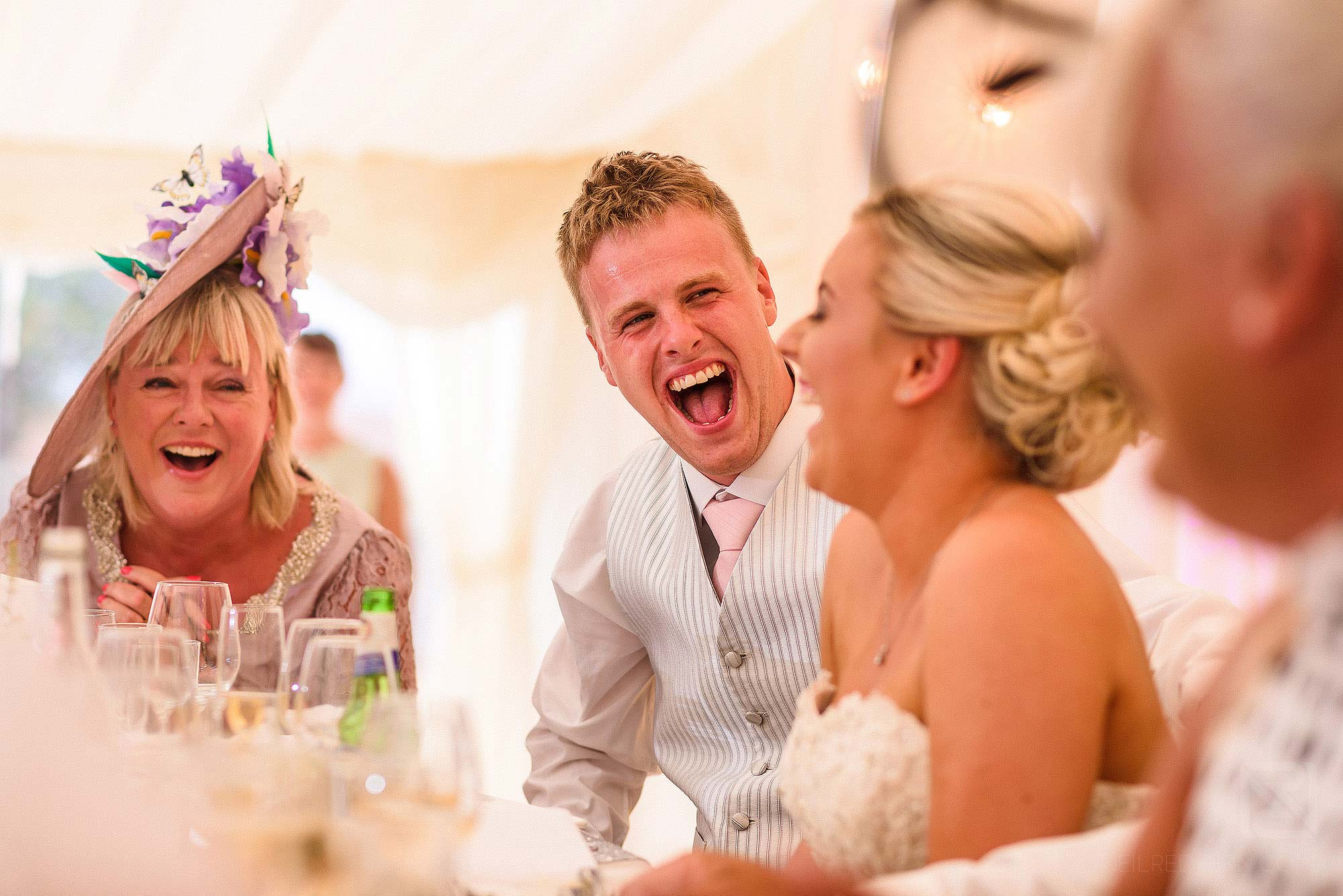 groom laughing during wedding speeches