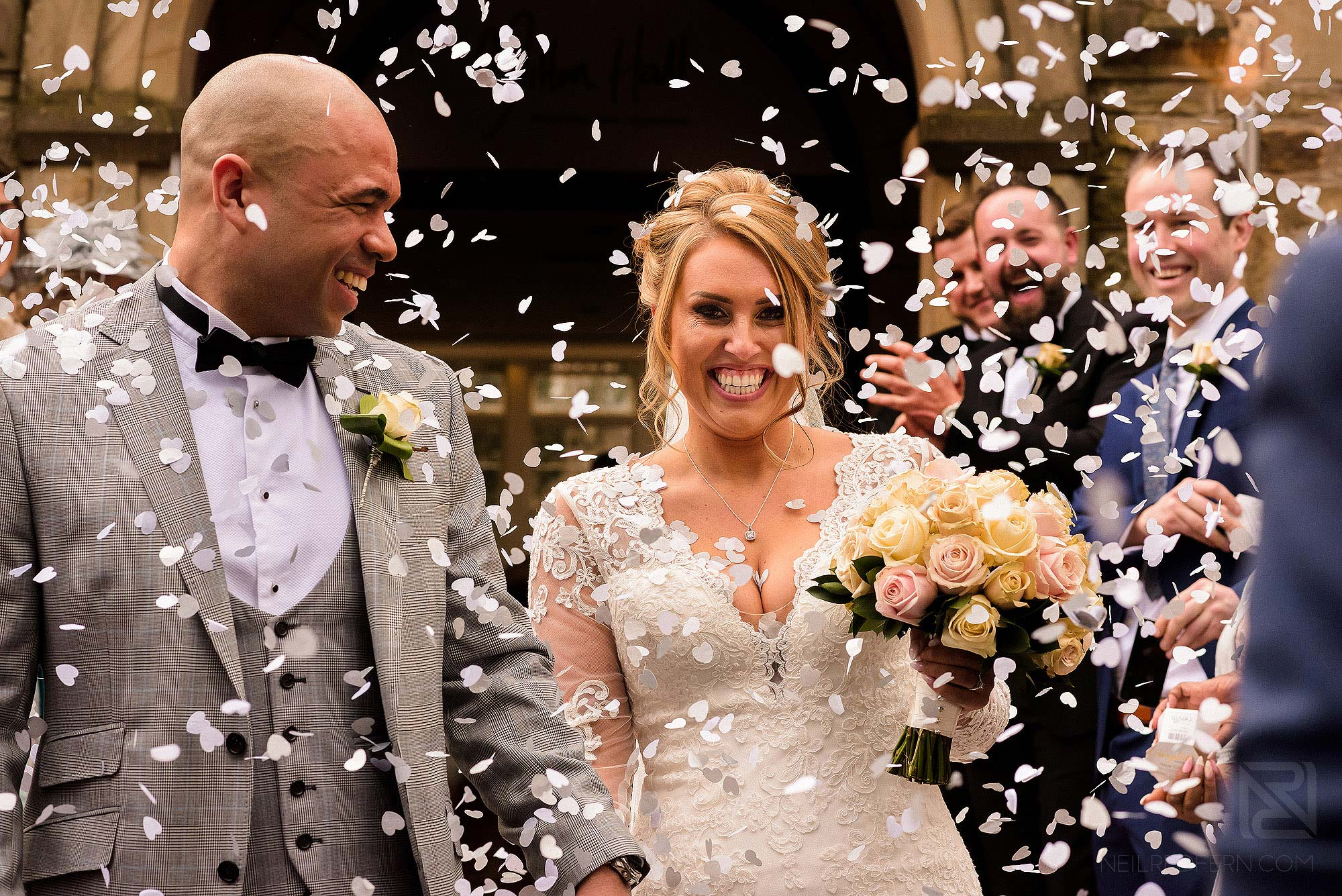 bride and groom walking through confetti at Mitton Hall