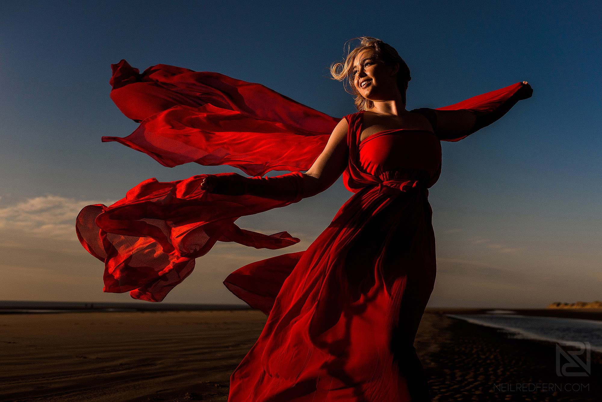 bride with flowing red dress on the beach