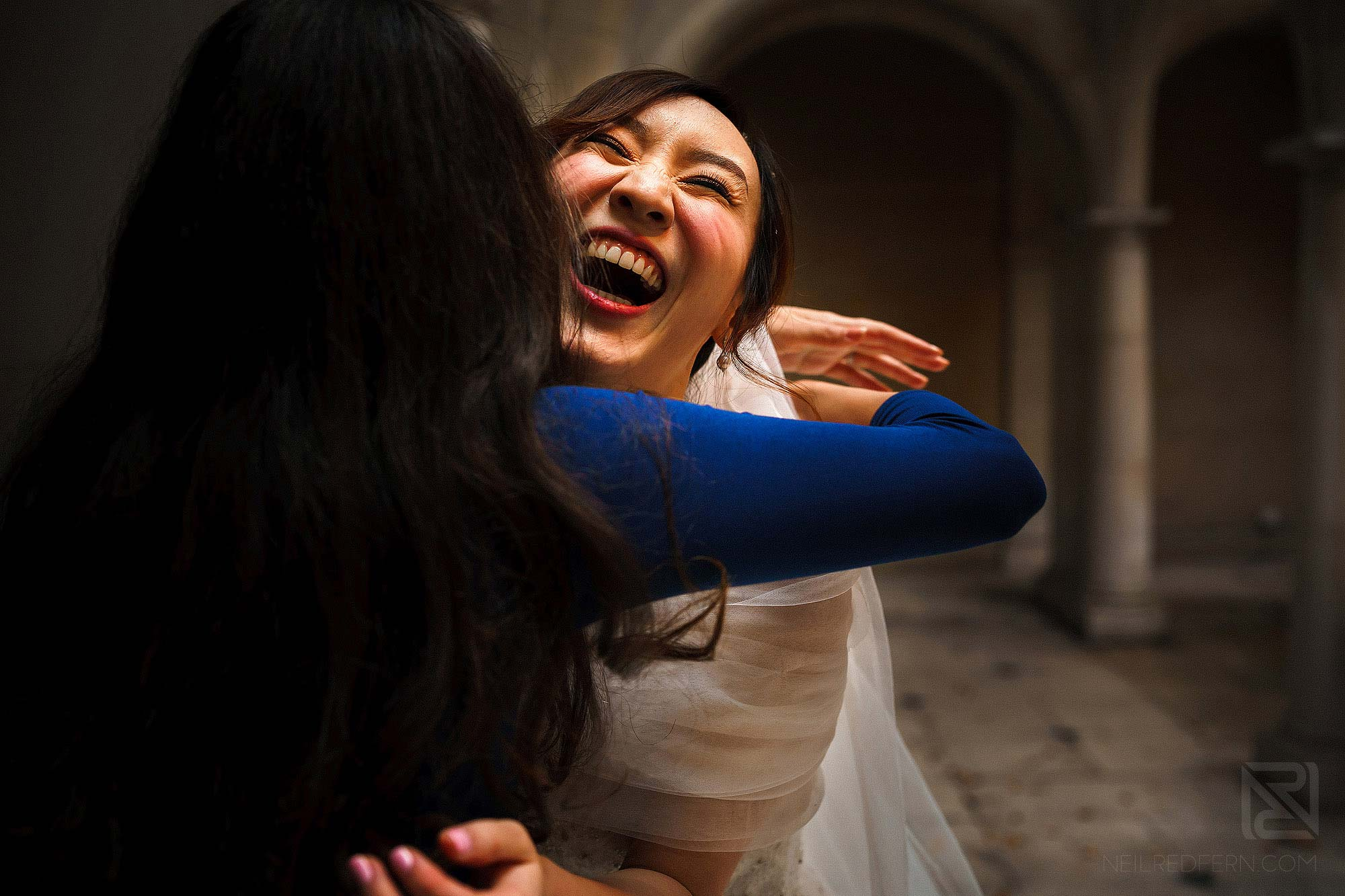 happy bride hugging friend after wedding ceremony
