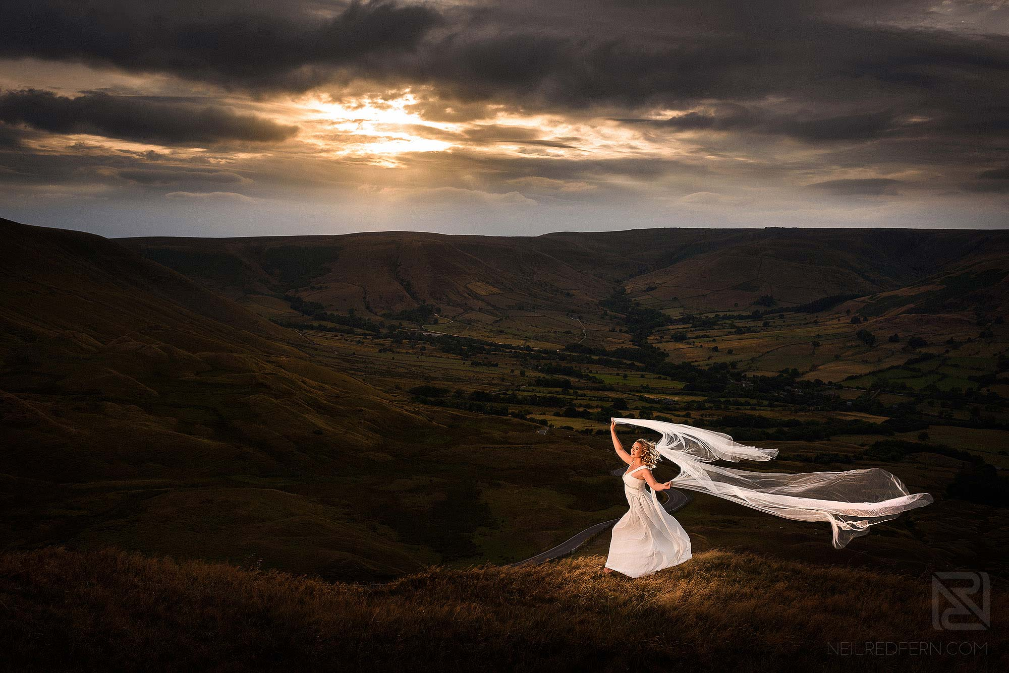 bride with long veil at Mam Tor in the Peak District