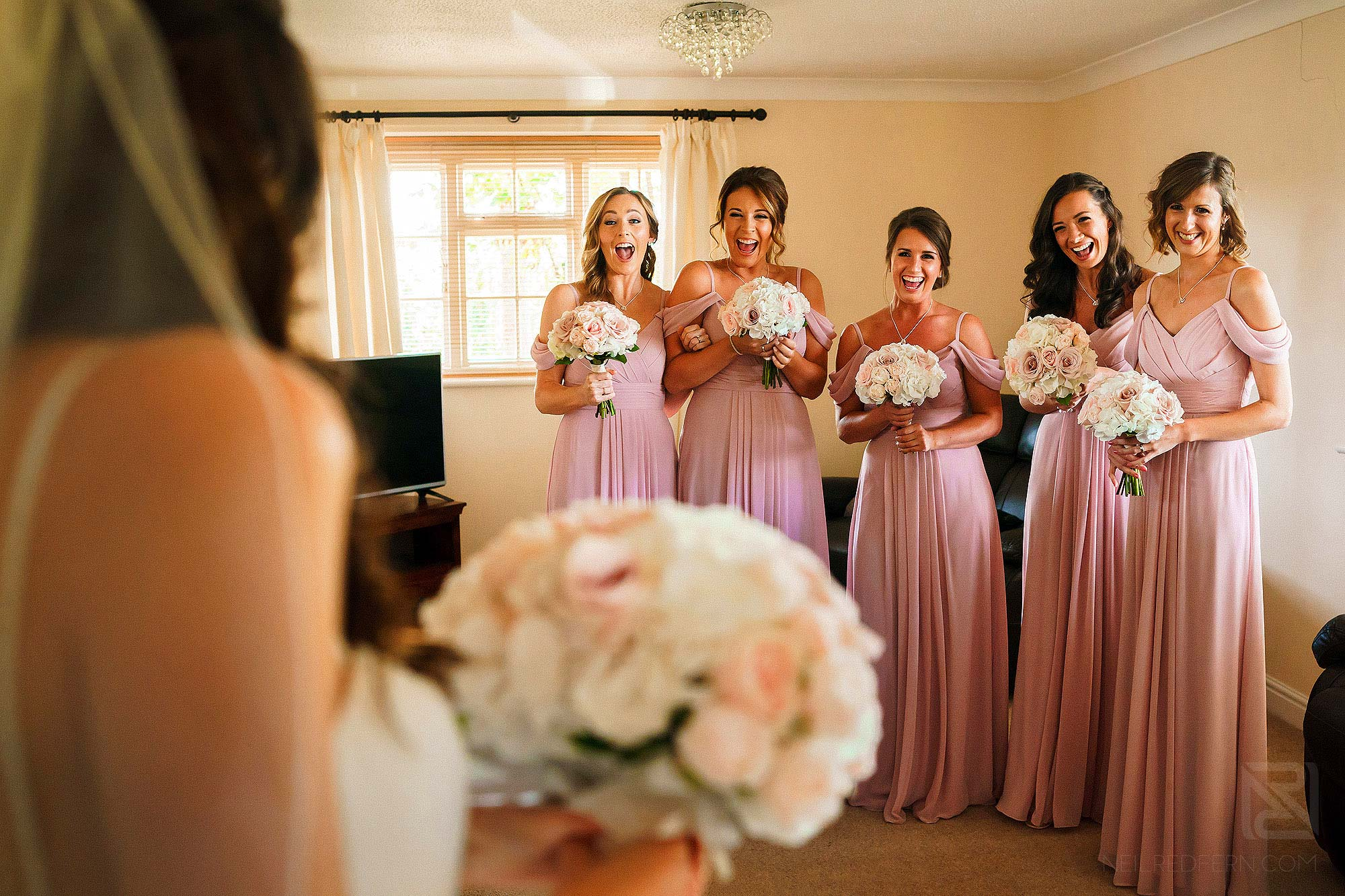 bridesmaids seeing bride in wedding dress for first time