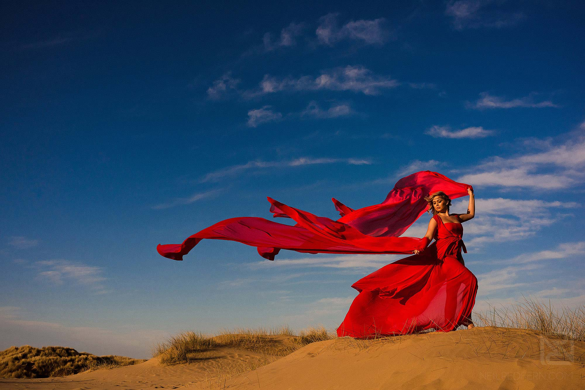 bride with long red dress on the beach at Formby