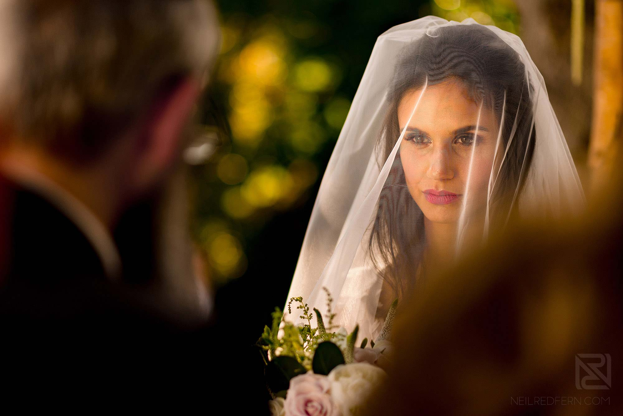 Jewish bride looking at Rabbi during wedding ceremony
