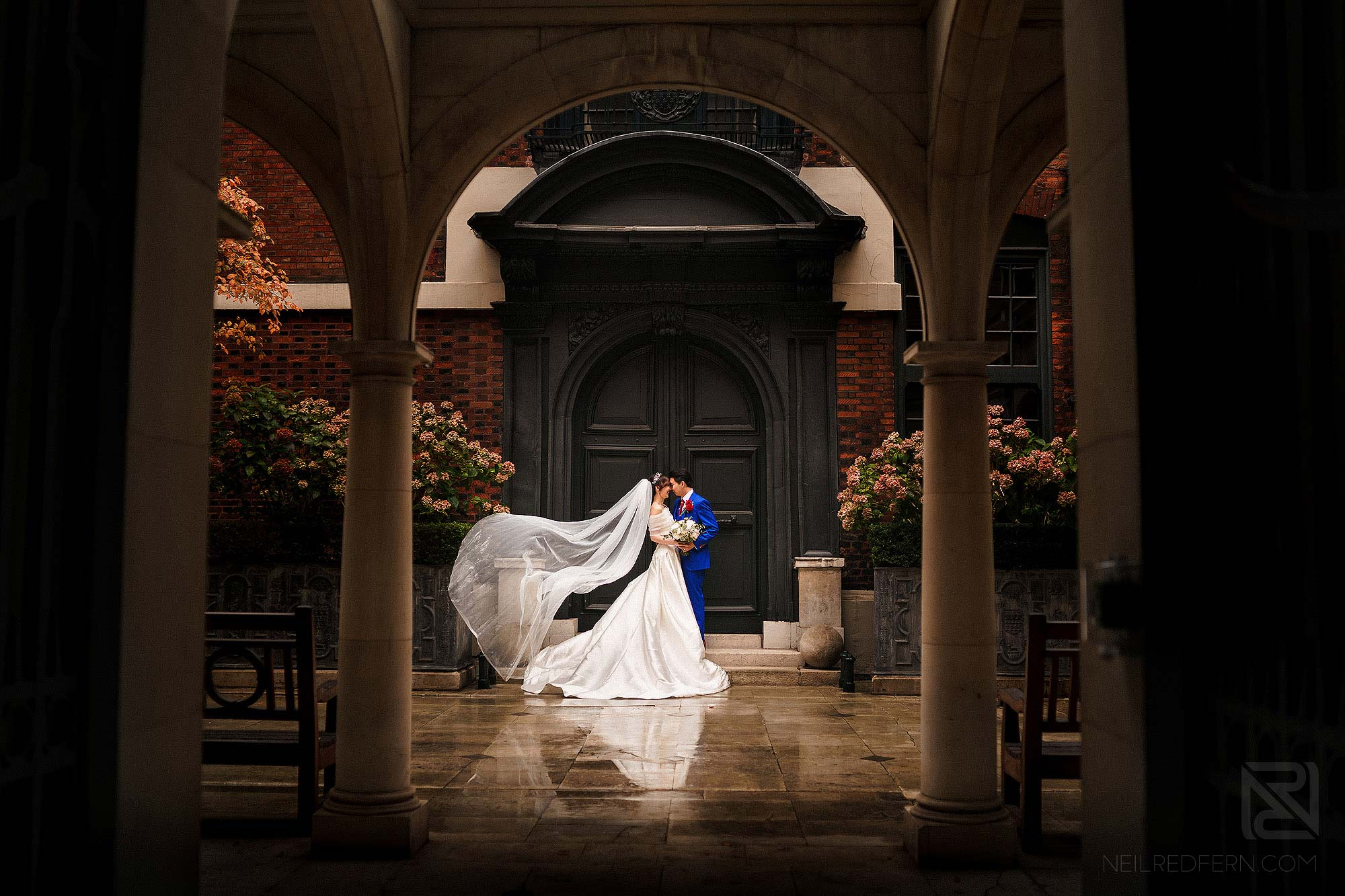 bride and groom with flowing veil at Skinners Hall in London