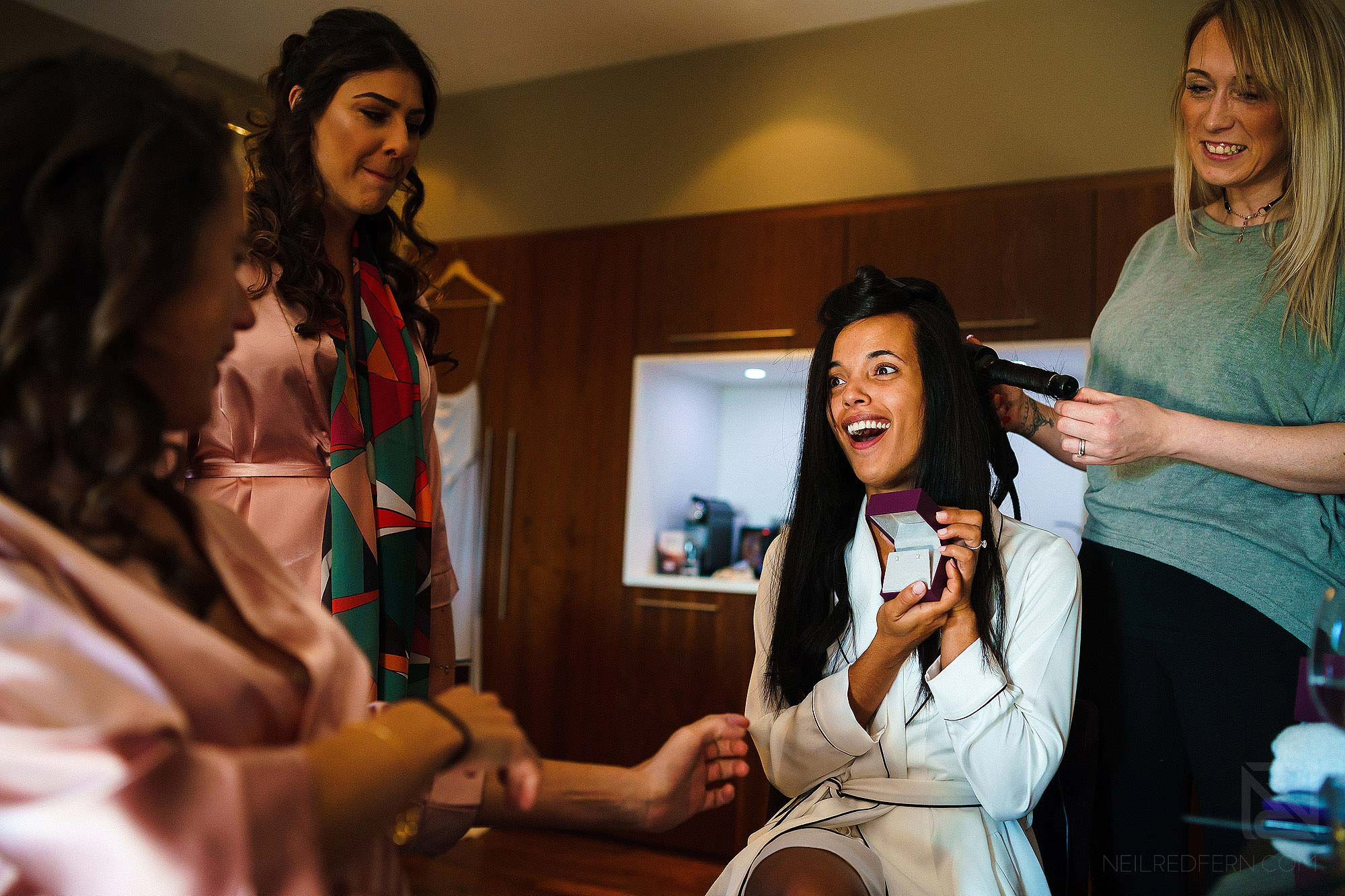 bride opening present from groom on morning of wedding