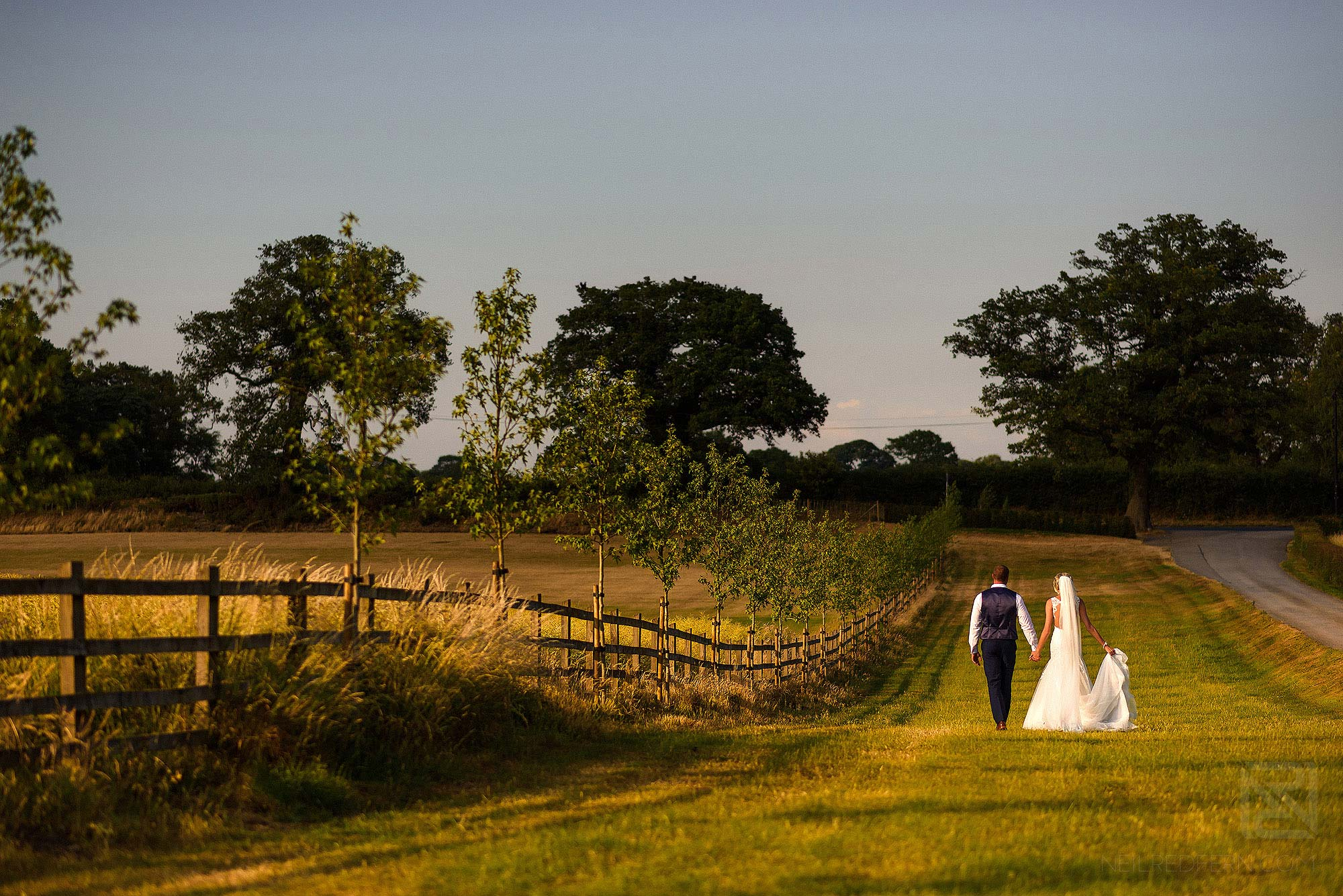 wide angle photograph of bride and groom at Sandhole Oak Barn