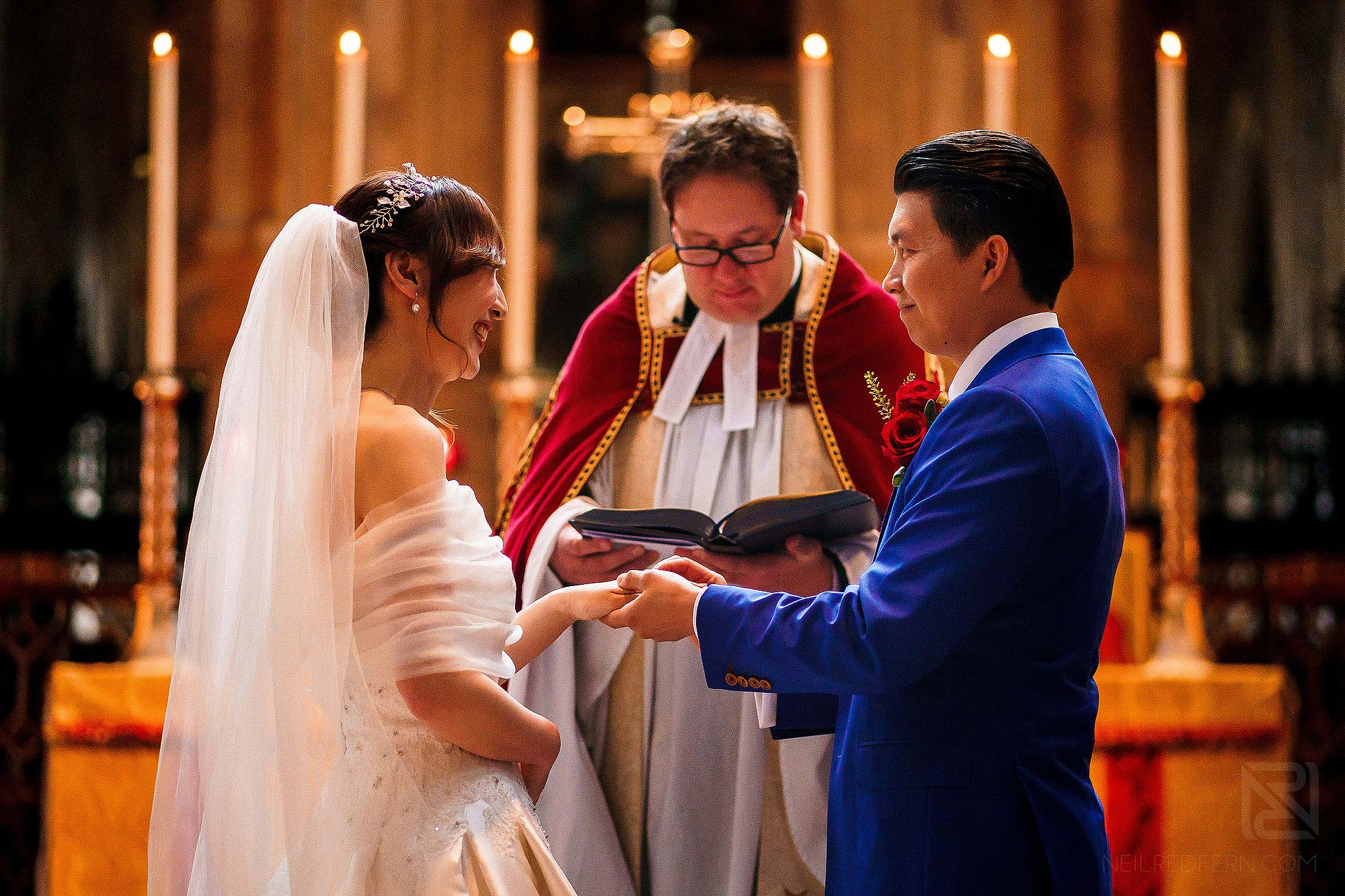 exchanging wedding vows during ceremony at St Bartholomew-the-Great in London