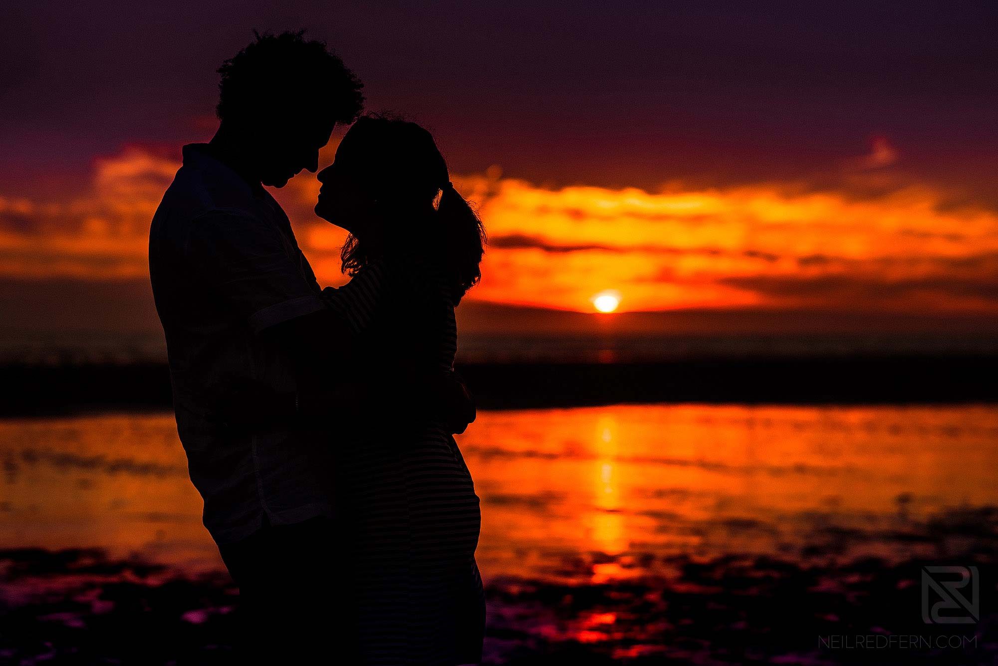 silhouette photograph of bride and groom on beach