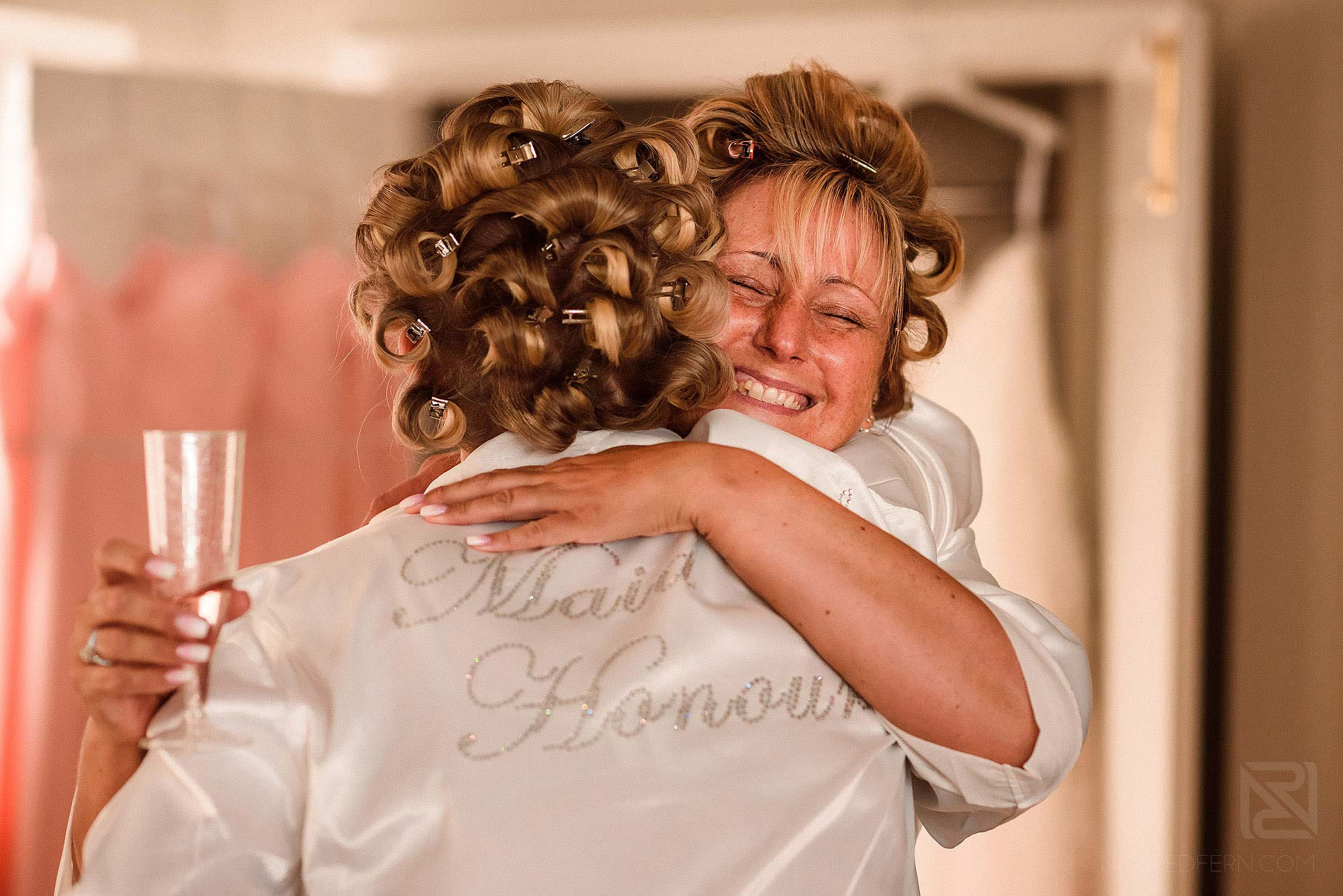 bride hugging friend whilst getting ready