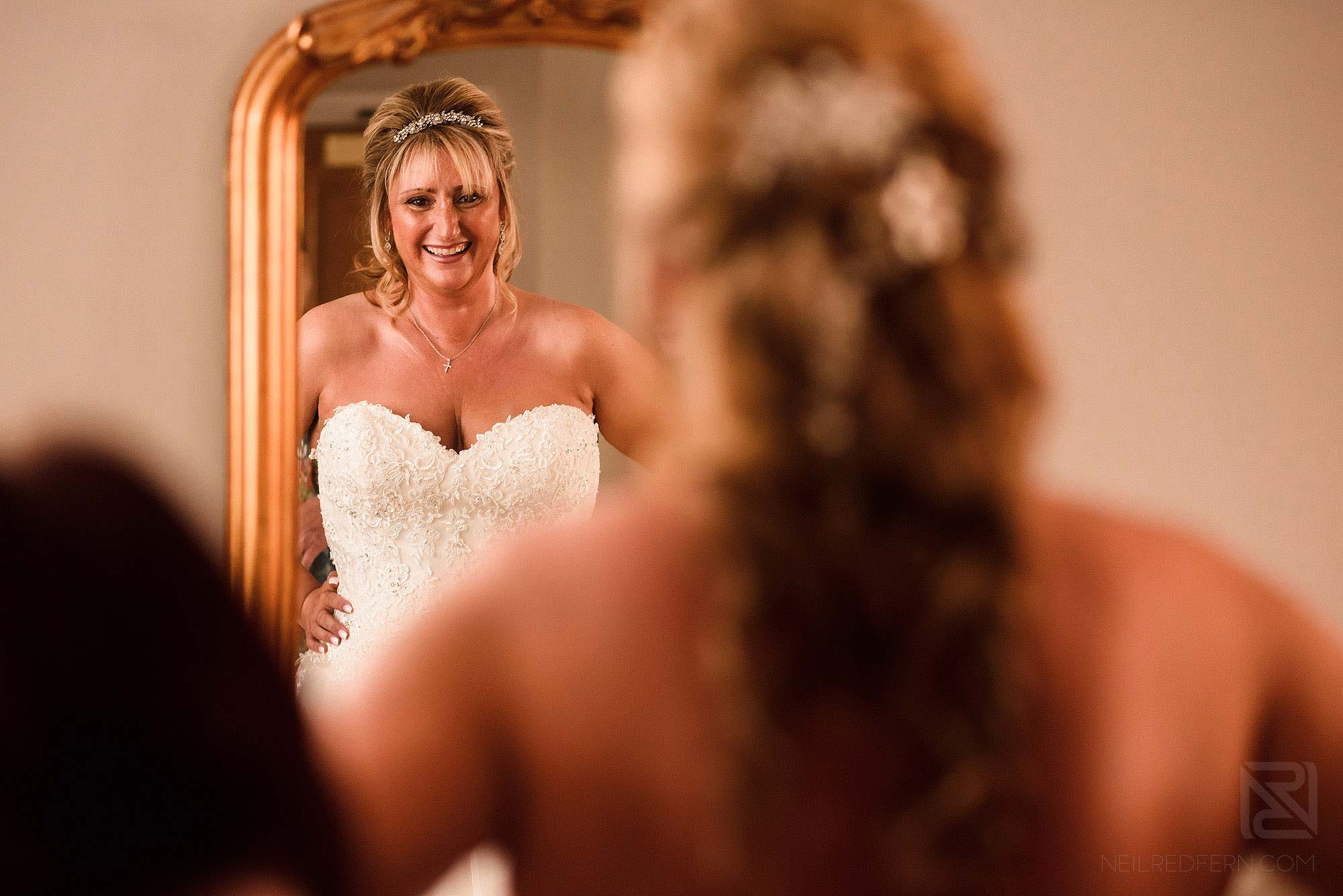 smiling bride looking in to mirror putting on wedding dress