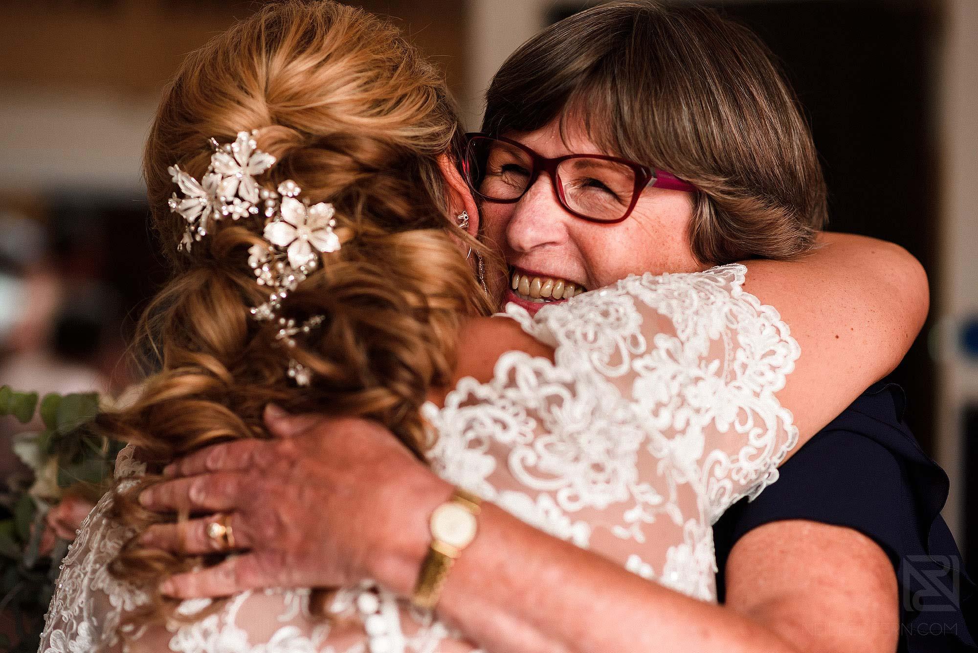emotional hug between friend and bride