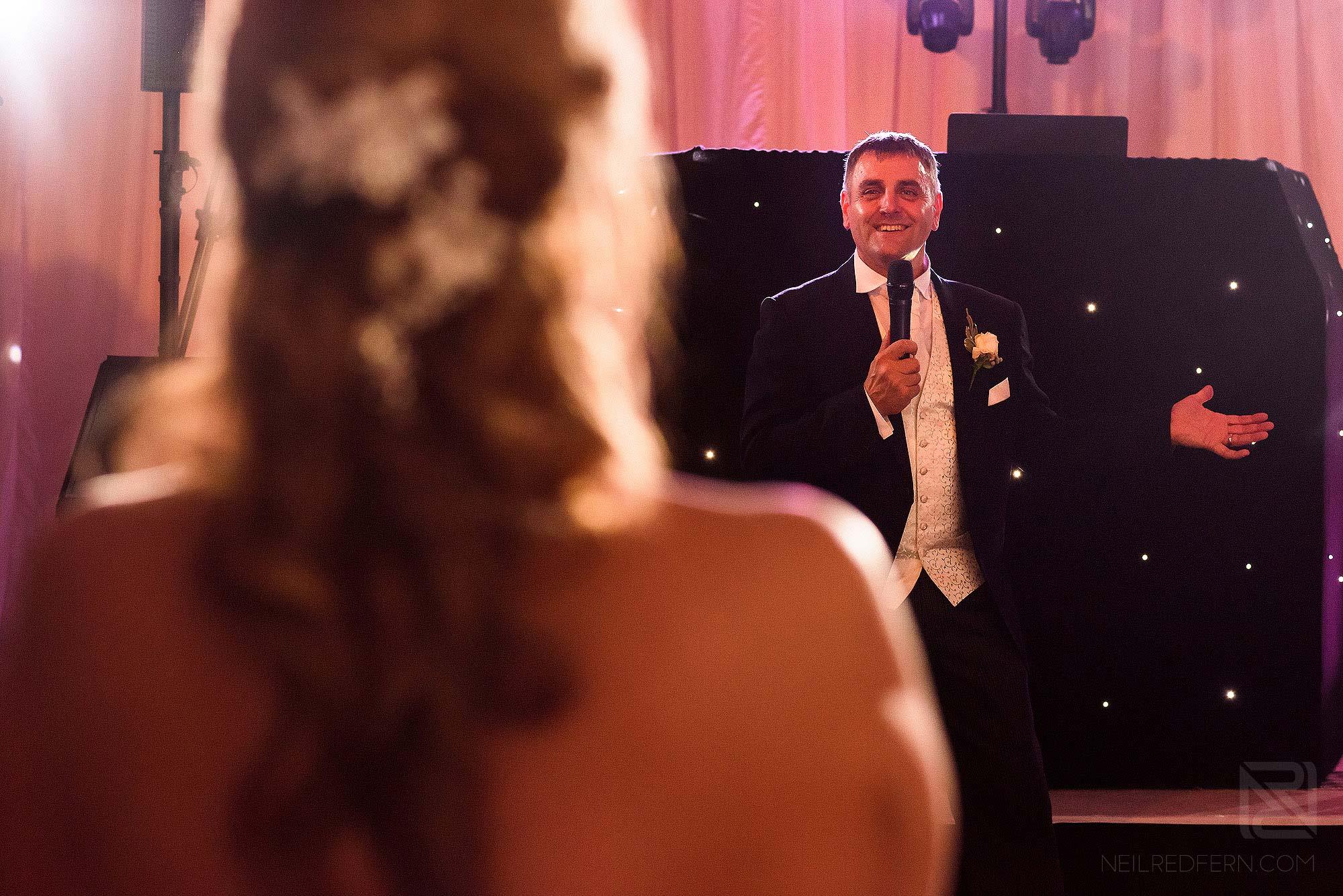 groom singing to bride during wedding reception