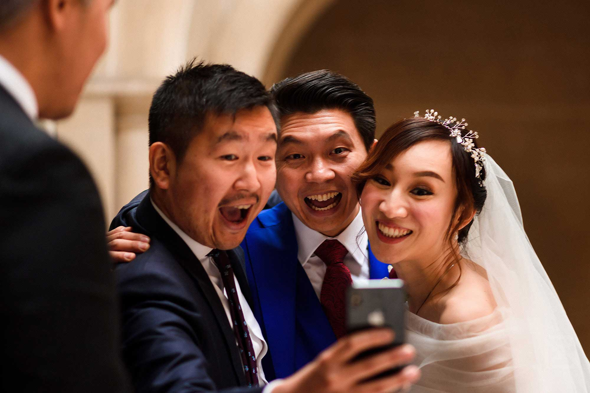 newlyweds laughing with guest
