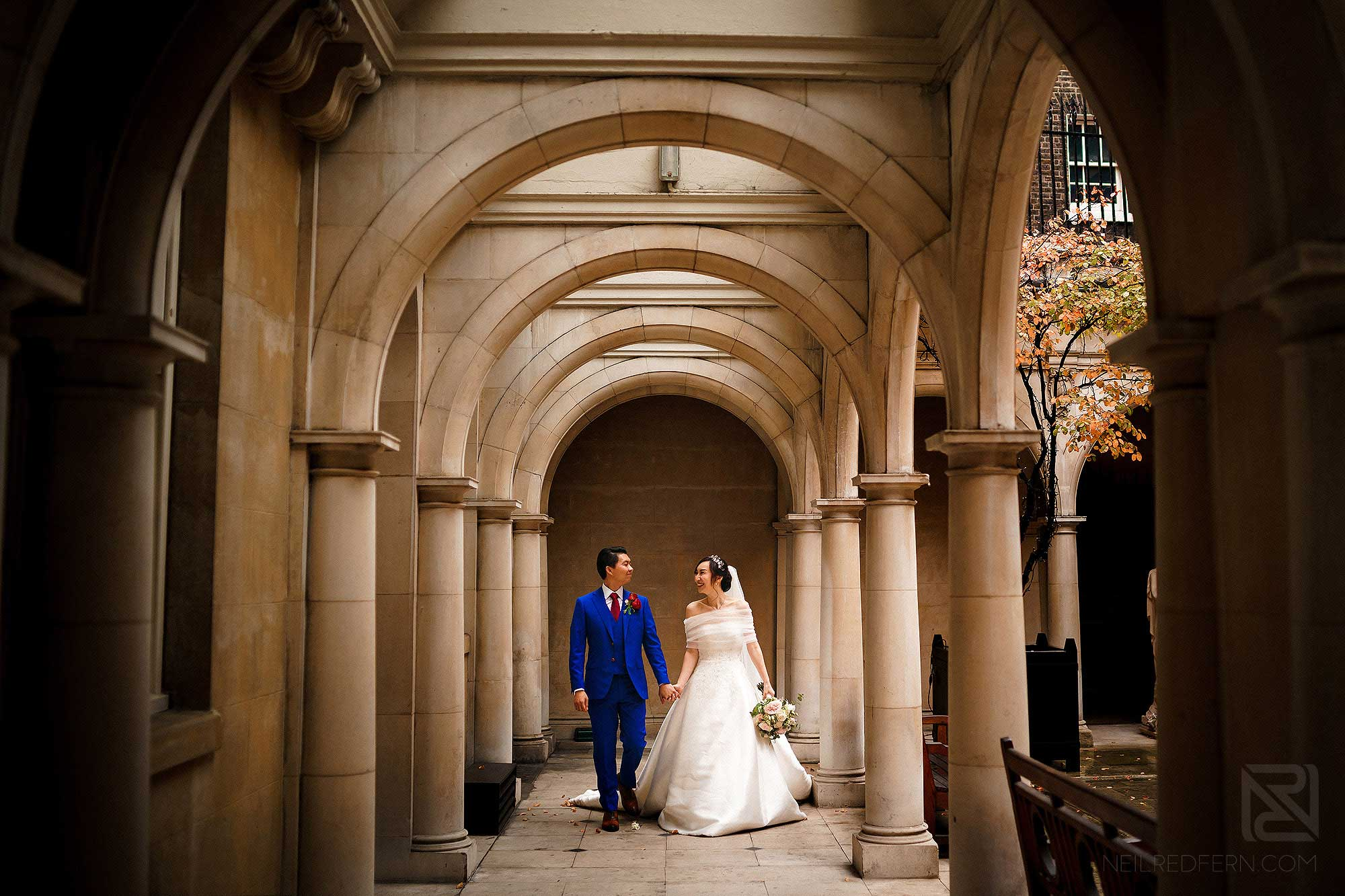 bride and groom walking together in Skinner's Hall in London