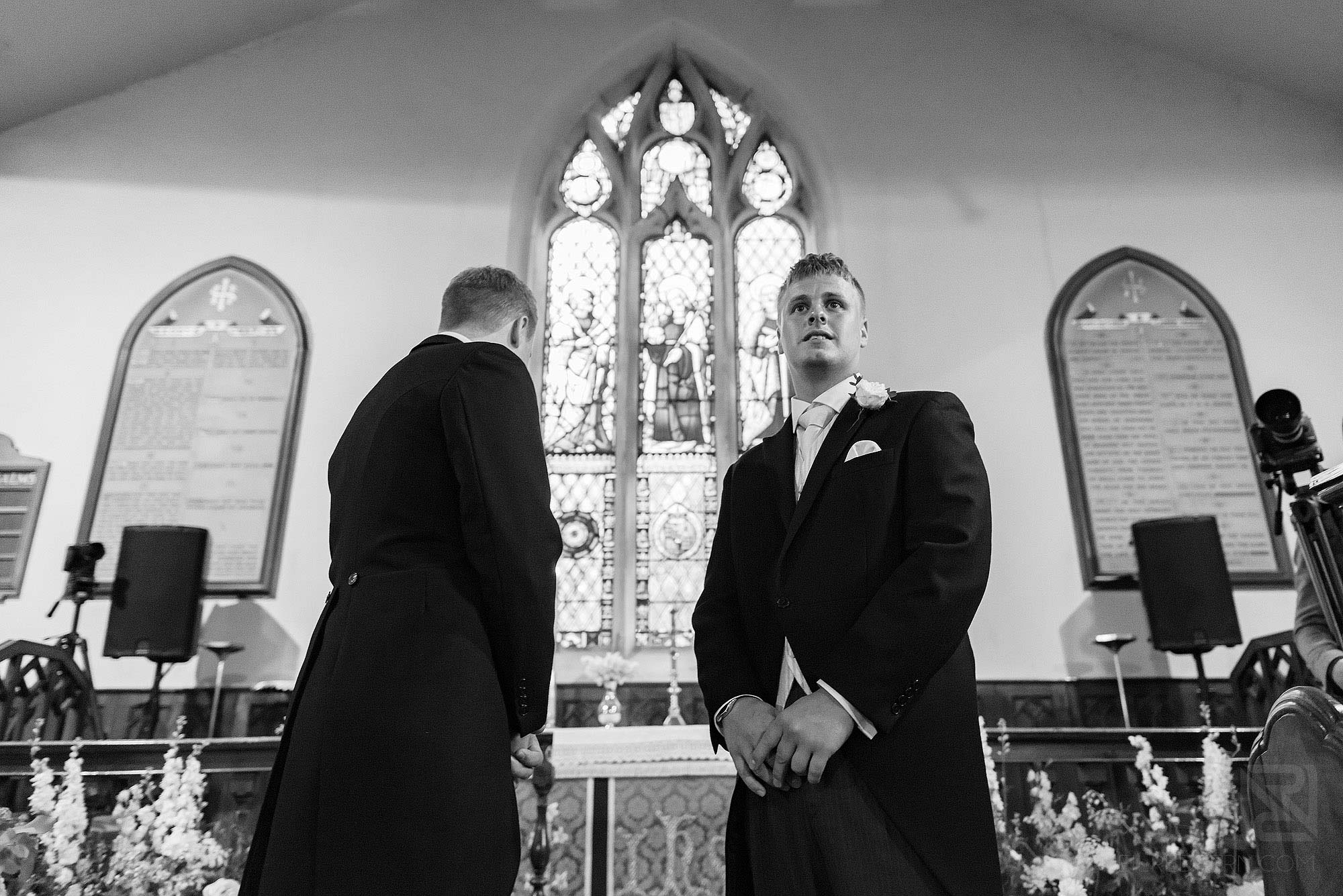 groom waiting at top of aisle