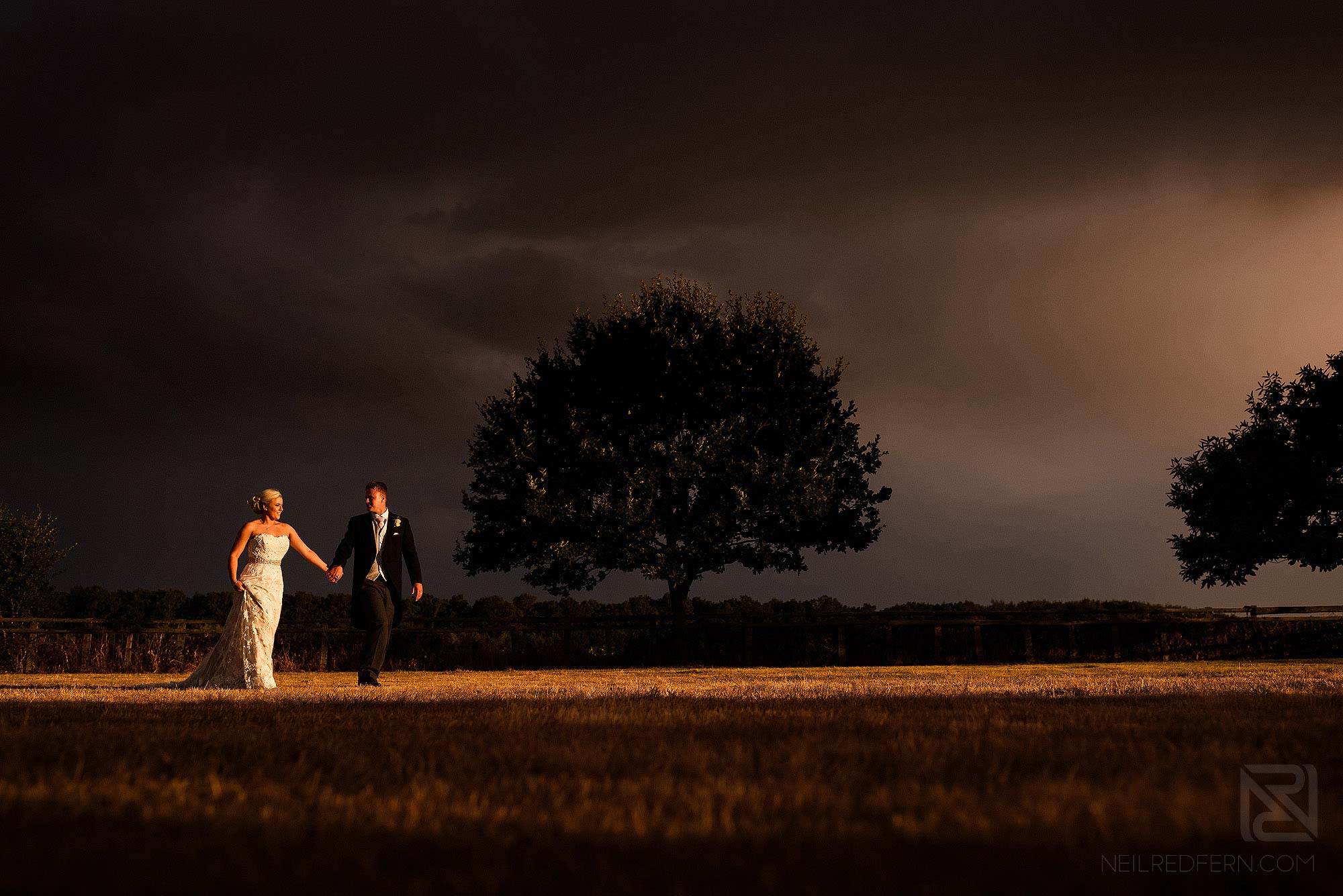bride and groom walking through countryside at sunset