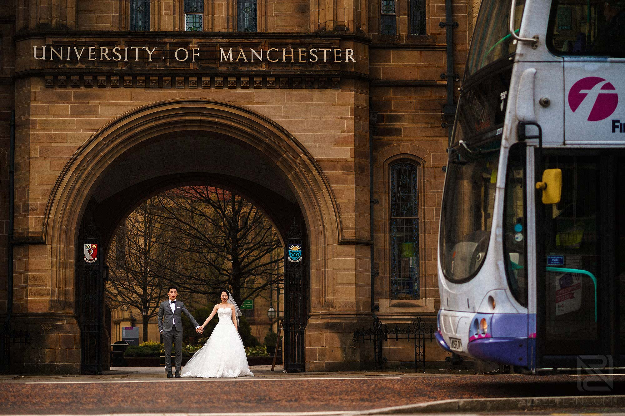 bride and groom outside University of Manchester