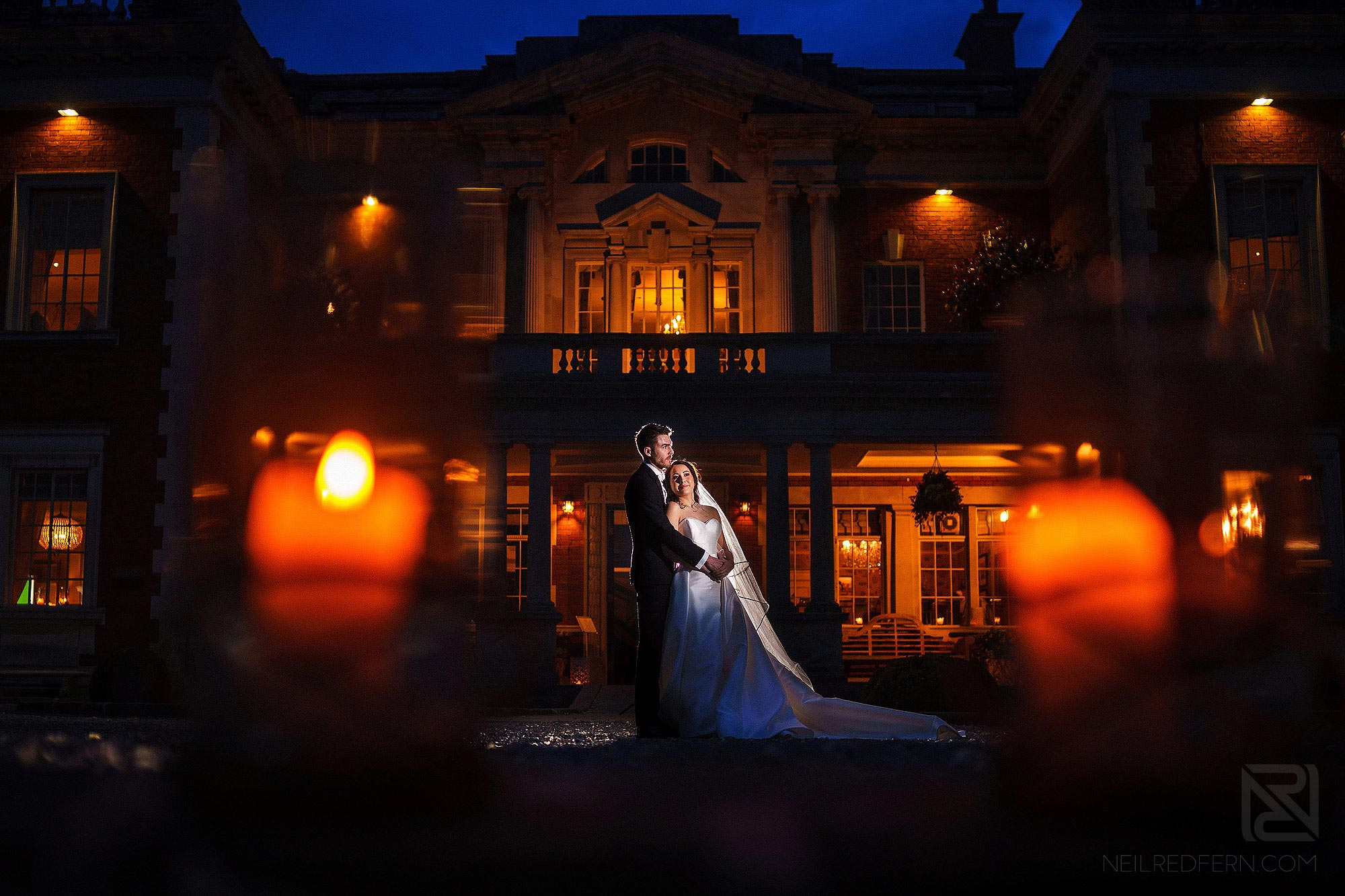 creative night time portrait of bride and groom outside Eaves Hall in Lancashire