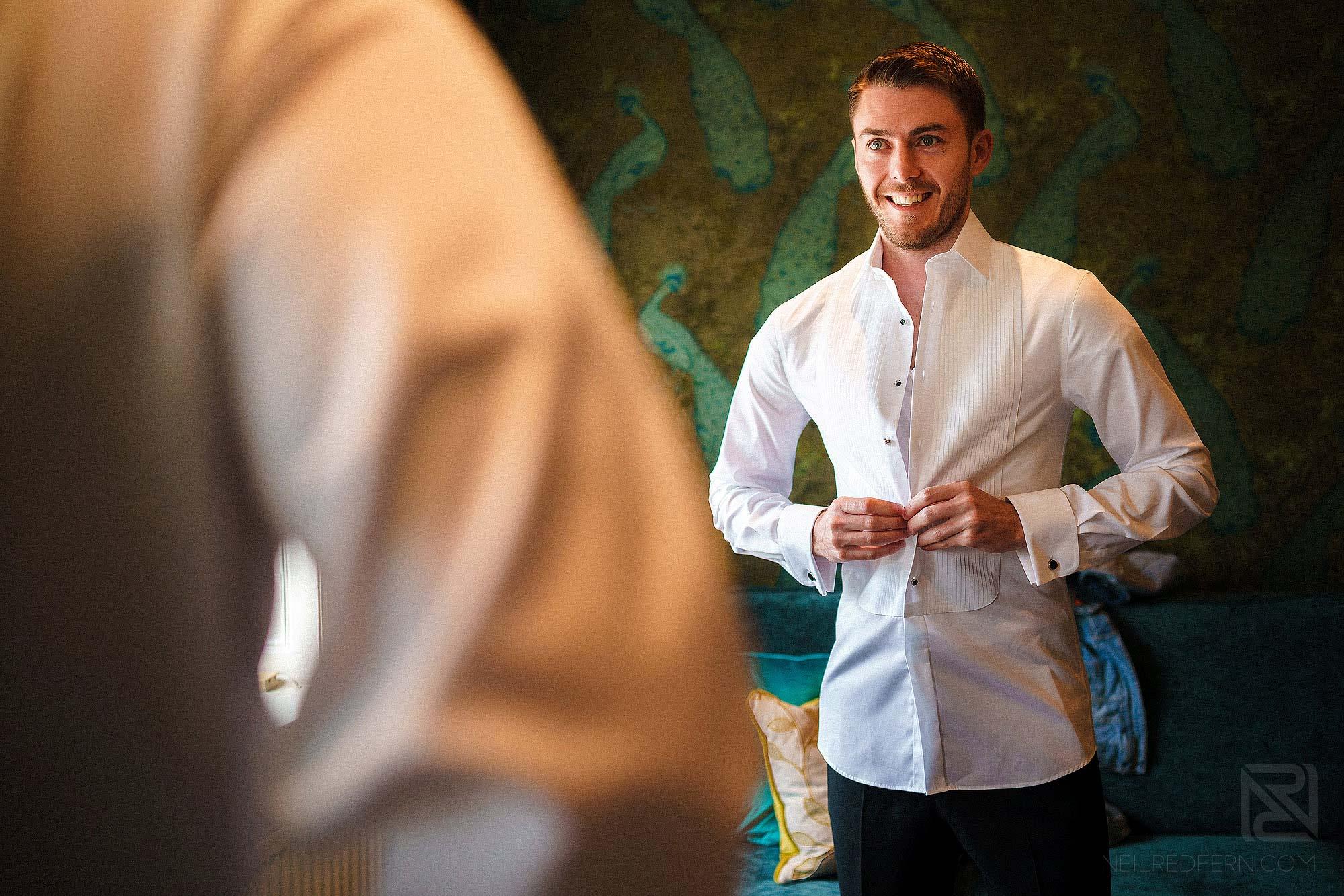groom putting on shirt
