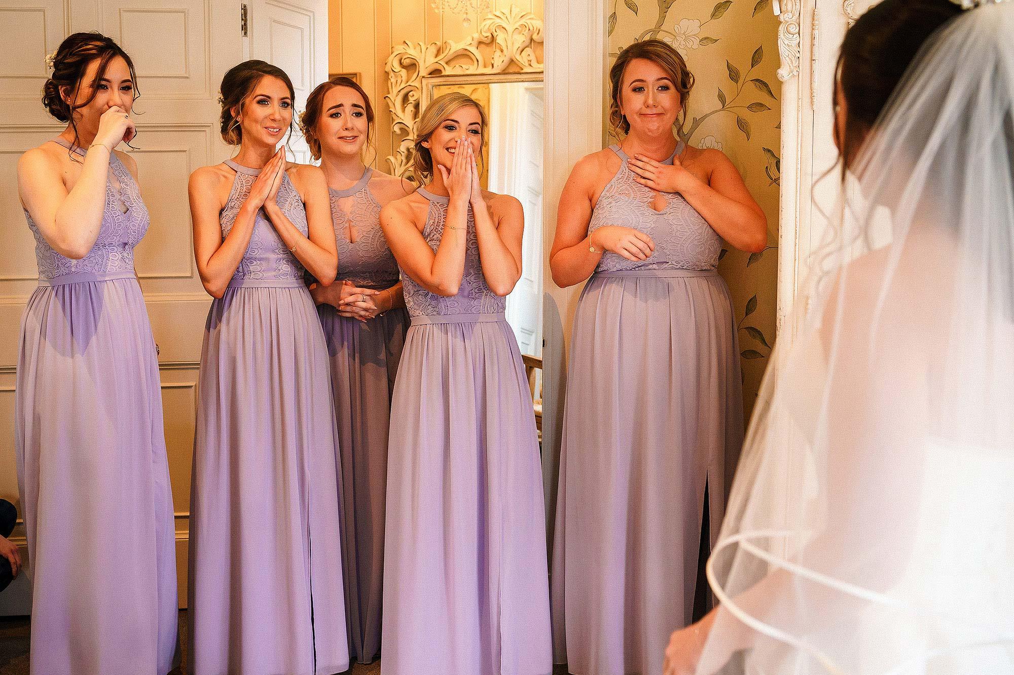 happy bridesmaids reacting to bride in wedding dress