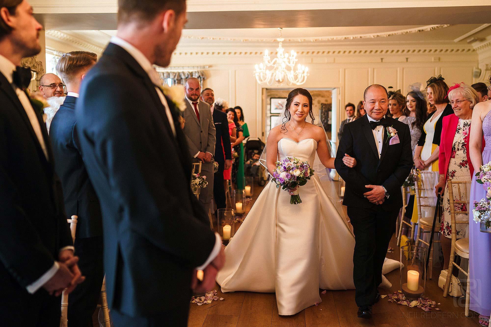 bride walking down the aisle at Eaves Hall