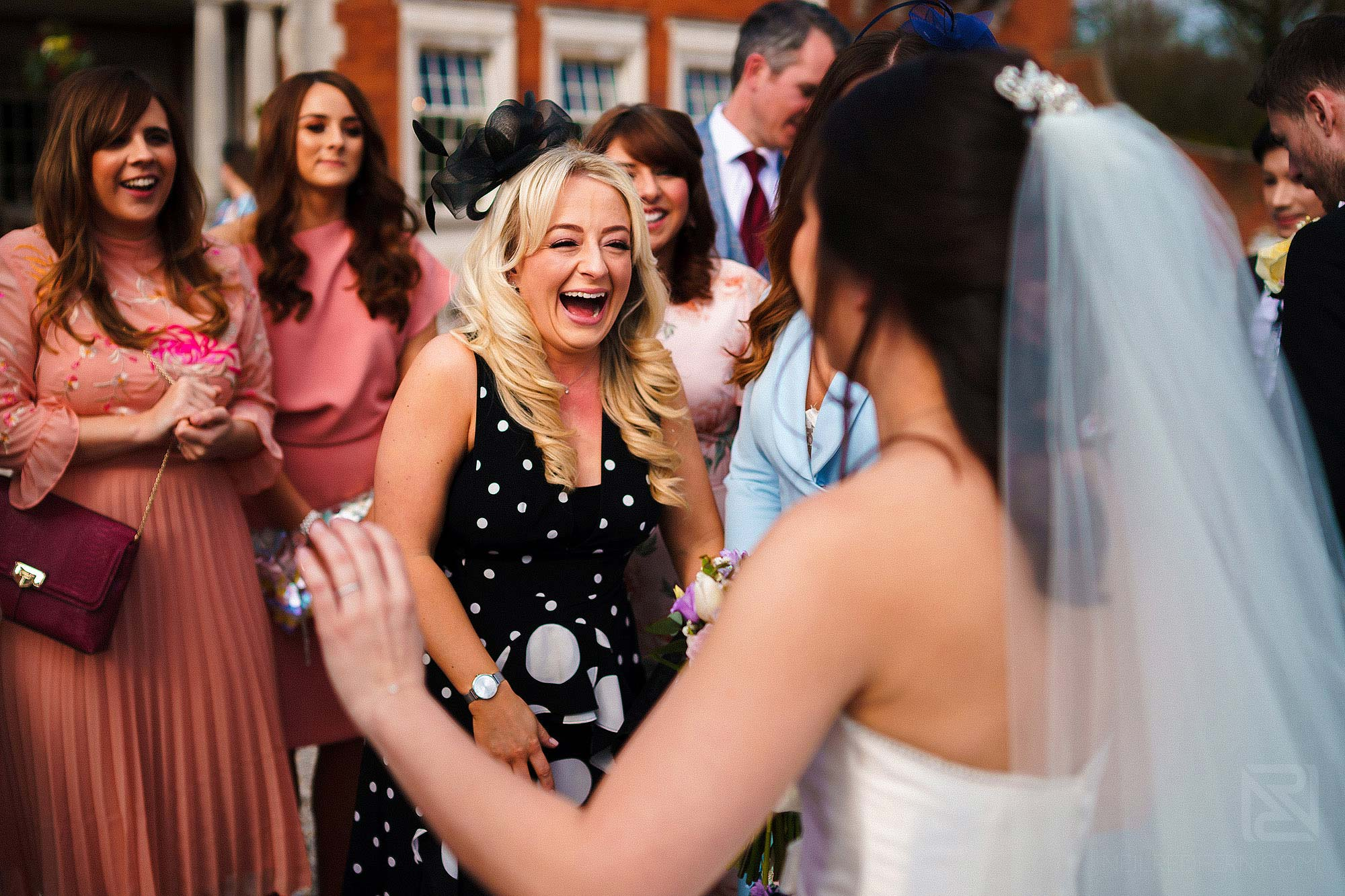 guests congratulating bride during Spring wedding at Eaves Hall