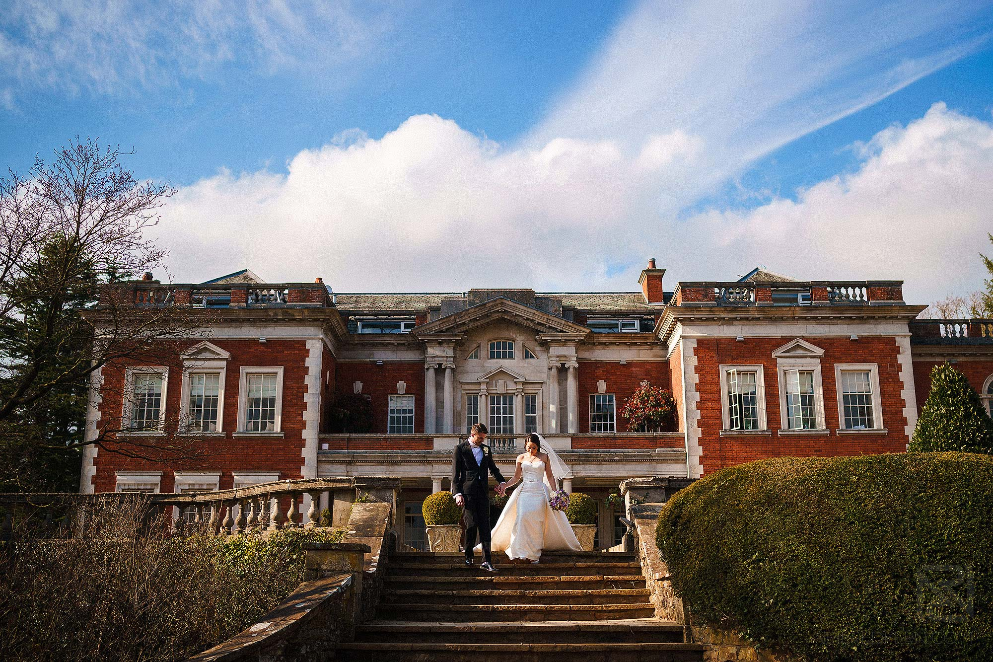 bride and groom walking down steps outside Eaves Hall in near Clitheroe