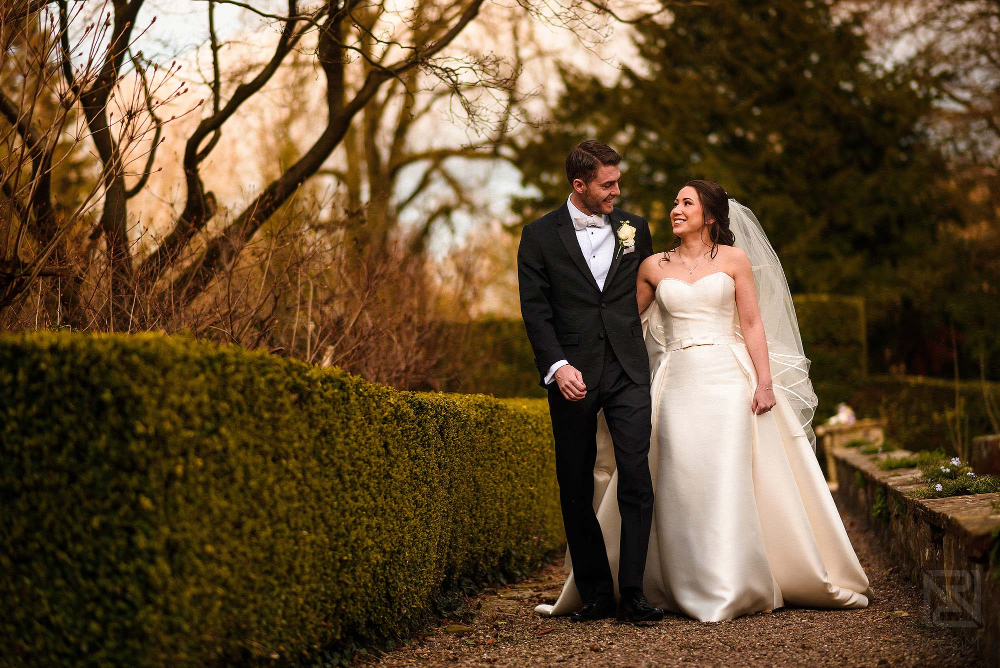 newlyweds walking through grounds of Eaves Hall
