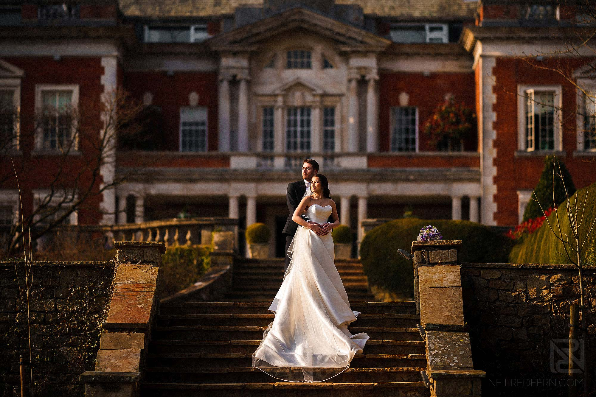 beautiful full length photograph of bride and groom outside Eaves Hall