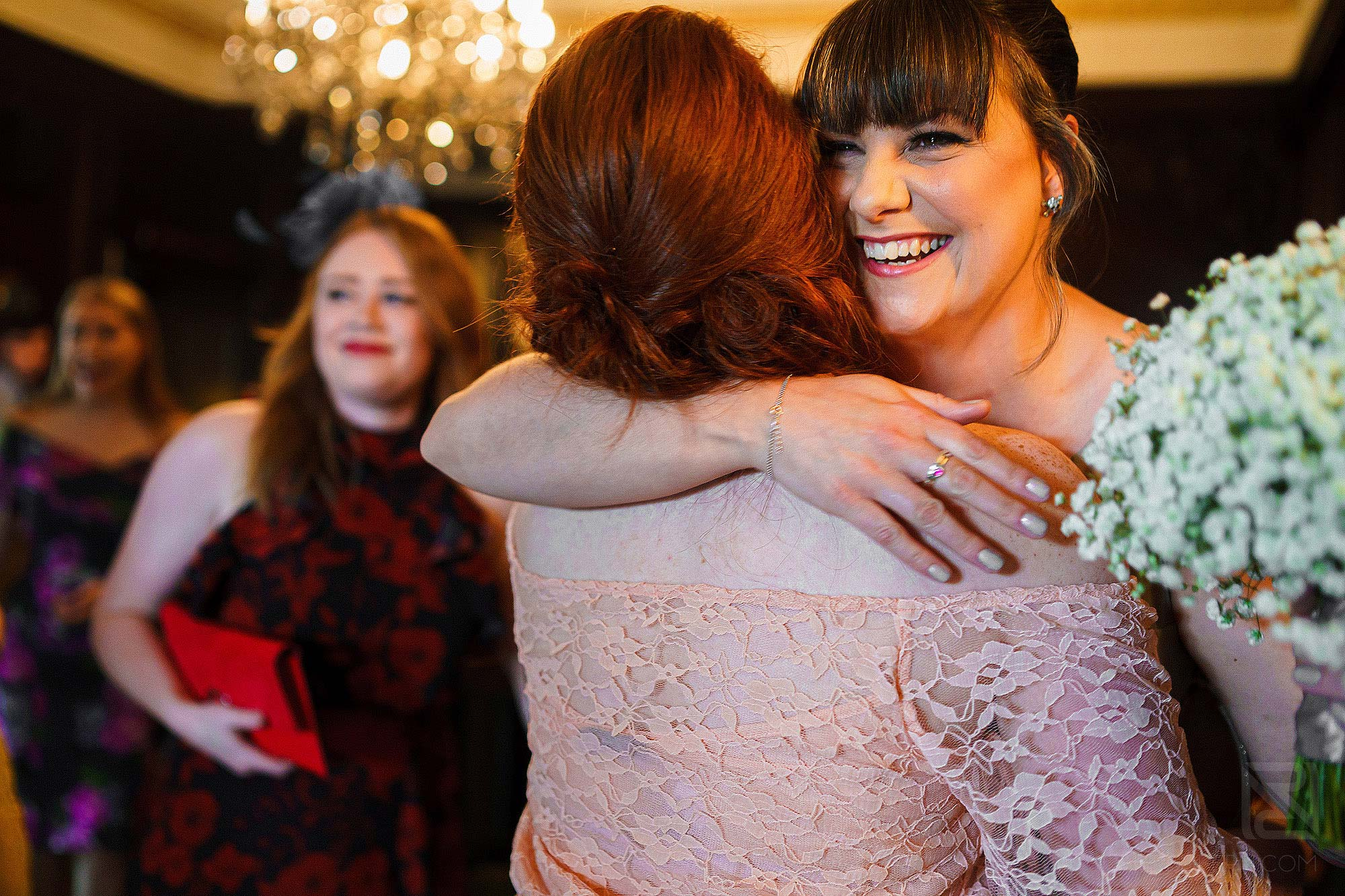happy bridesmaid hugging wedding guest