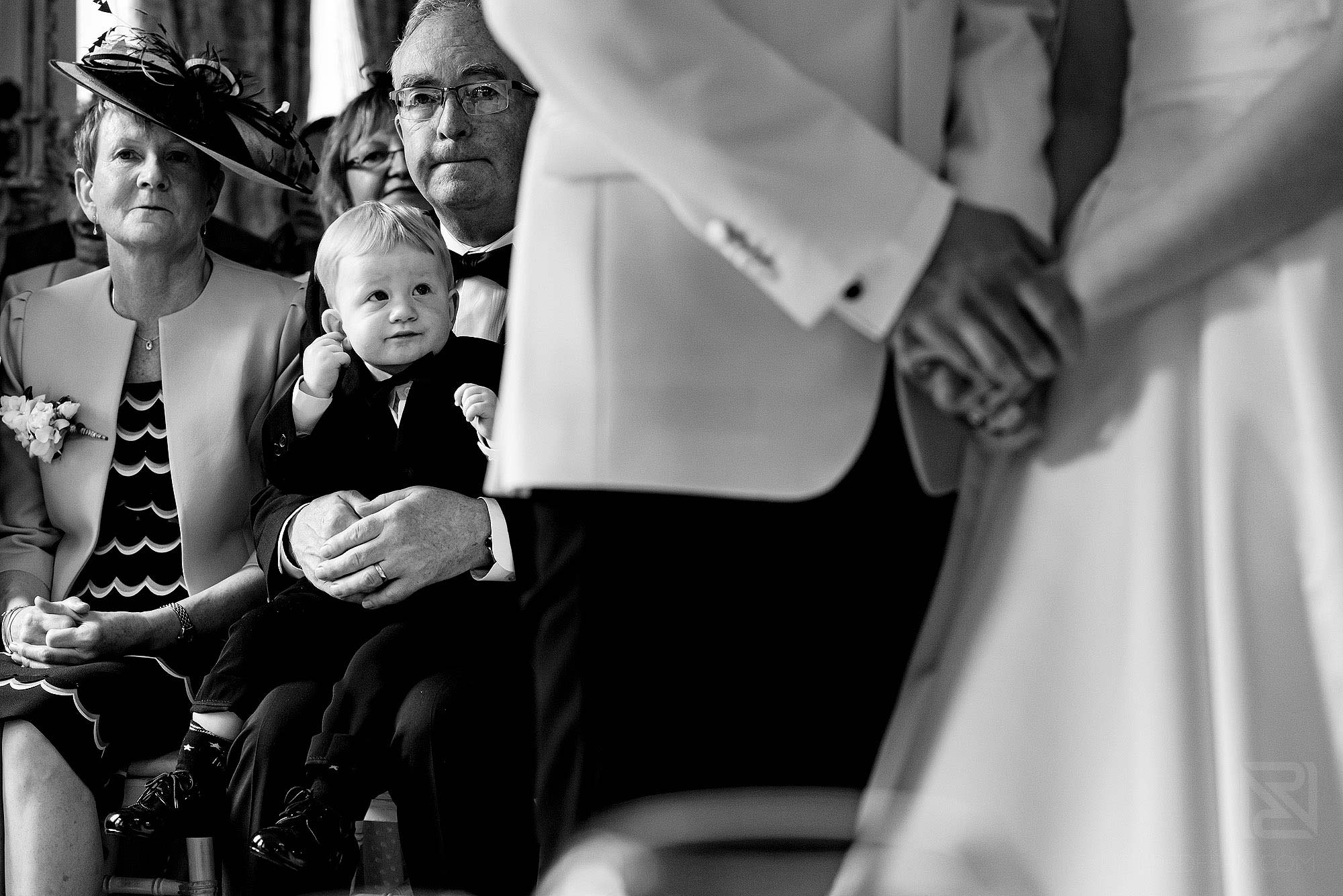 little page boy looking at bride and groom