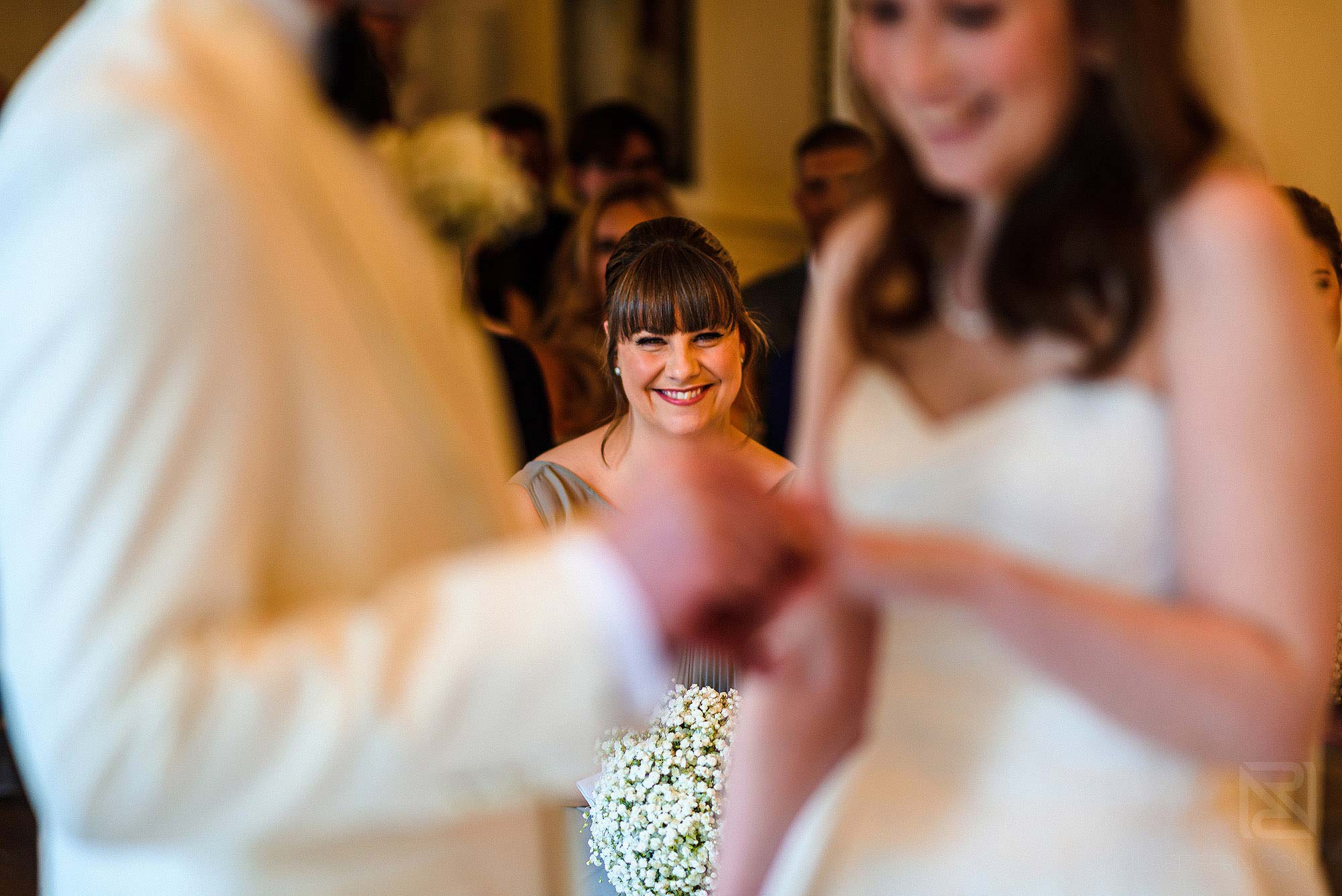 bridesmaid smiling as bride and groom exchange wedding rings