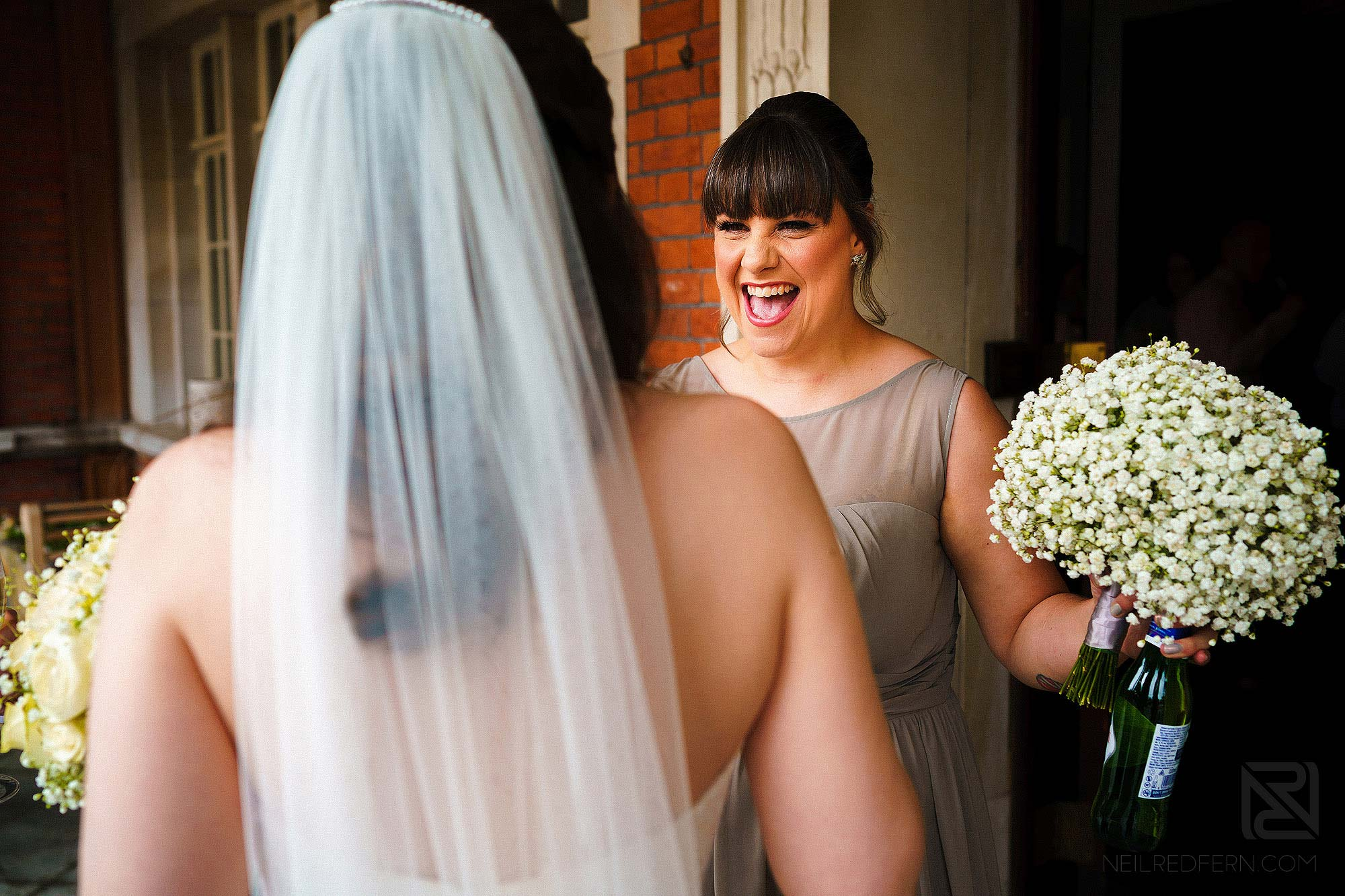 bridesmaid congratulating bride after wedding ceremony at Eaves Hall