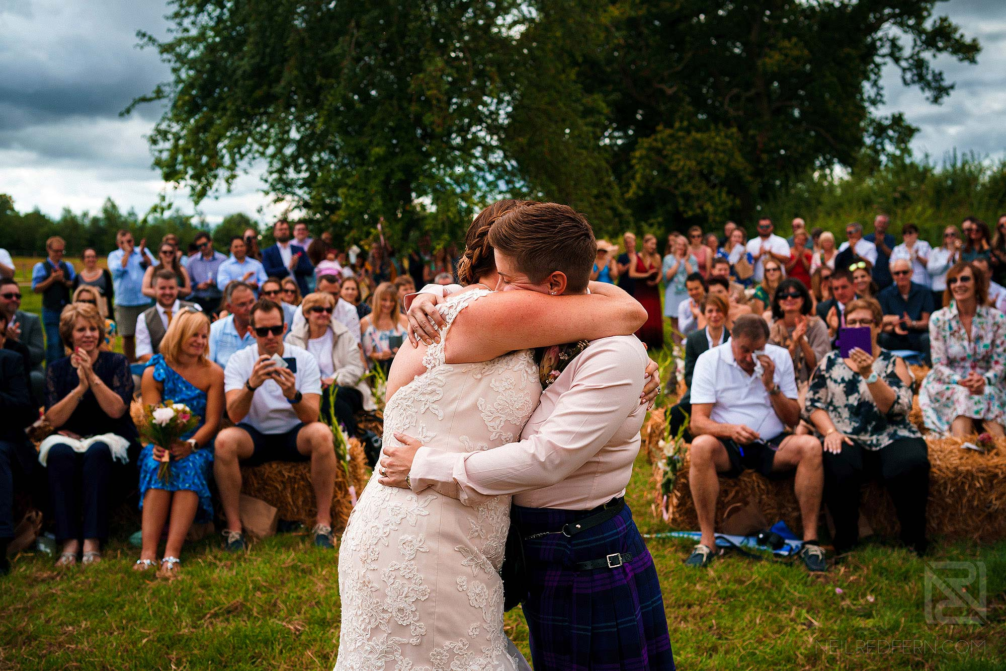 two bride hugging during wedding ceremony on farm
