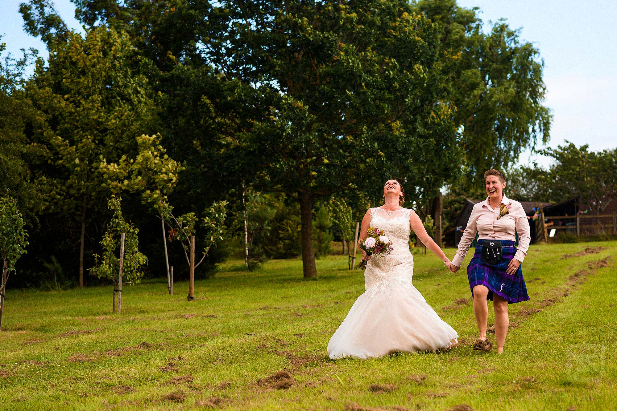 two brides walking towards wedding ceremony on farm