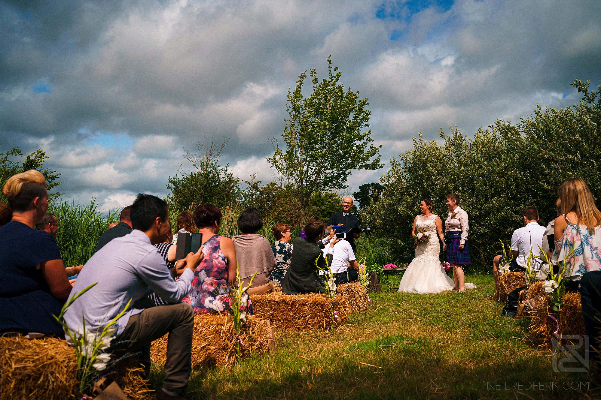 wide angle photograph of outside wedding ceremony on farm