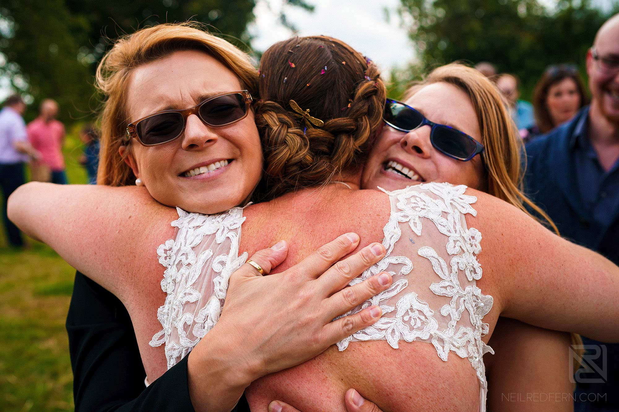bride hugging two friends