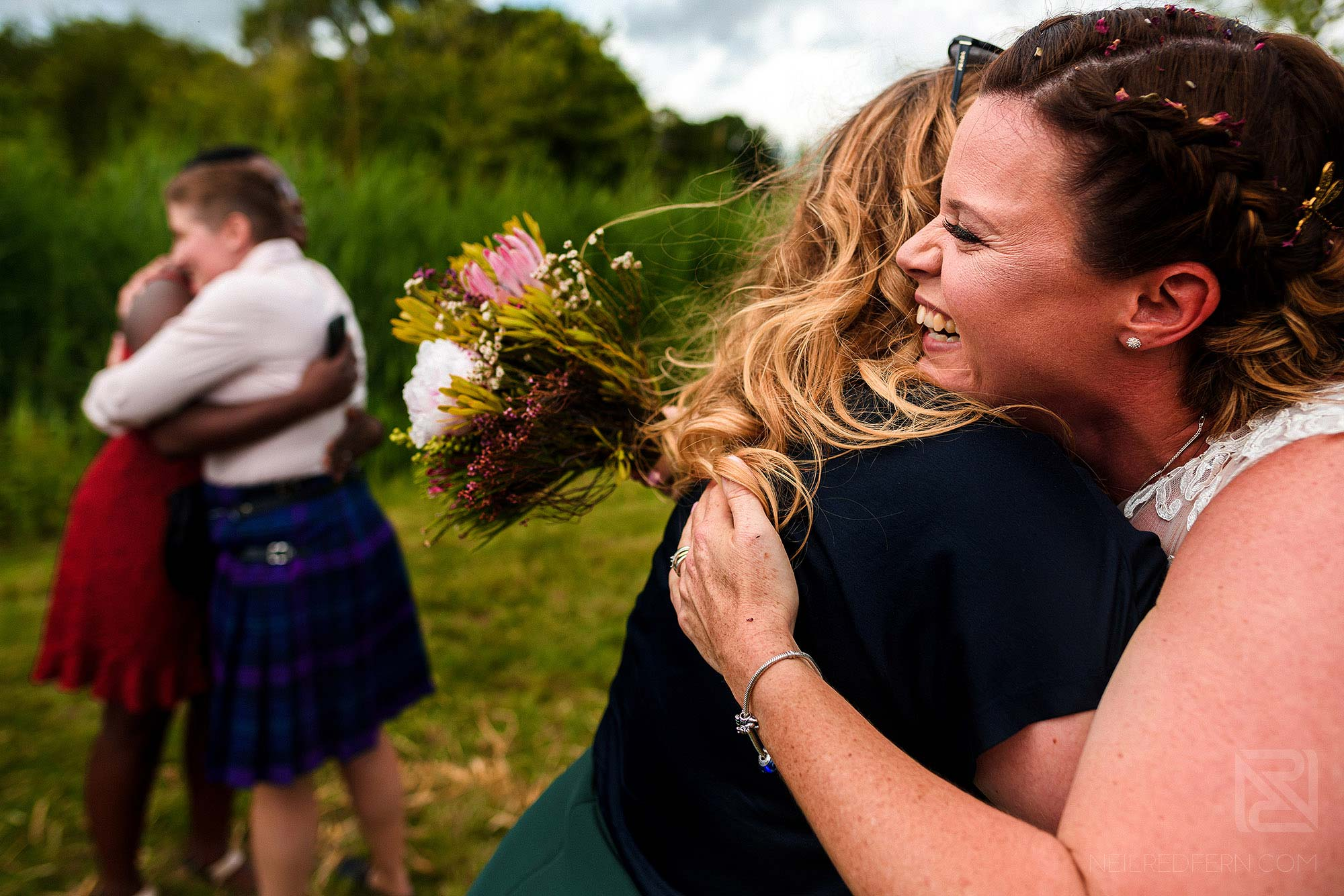 brides hugging friends at farm wedding