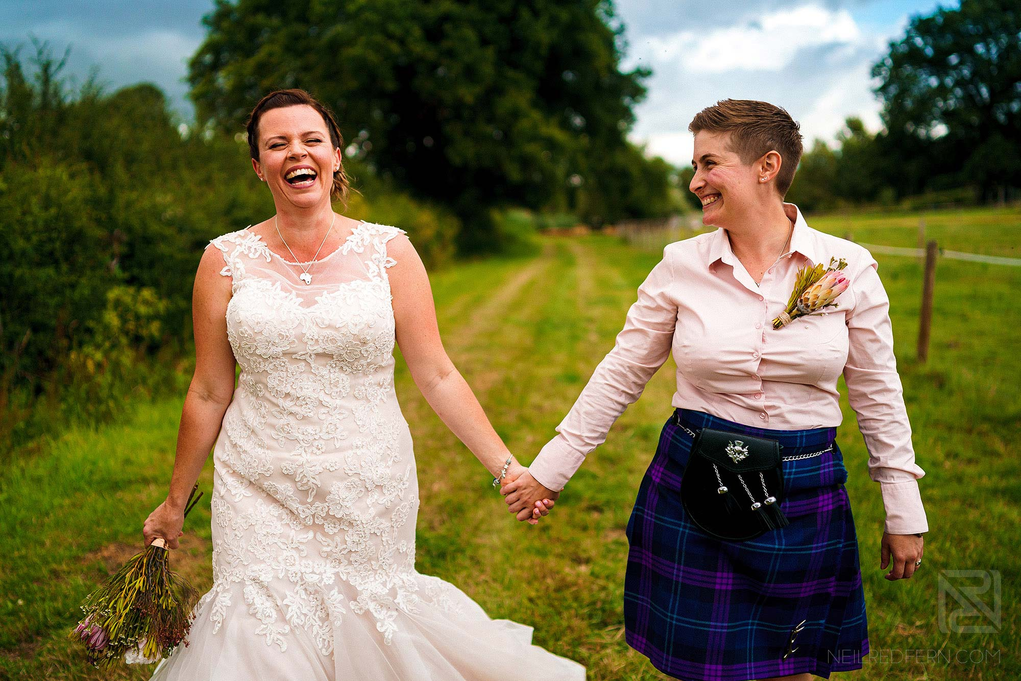 brides laughing whilst holding hands