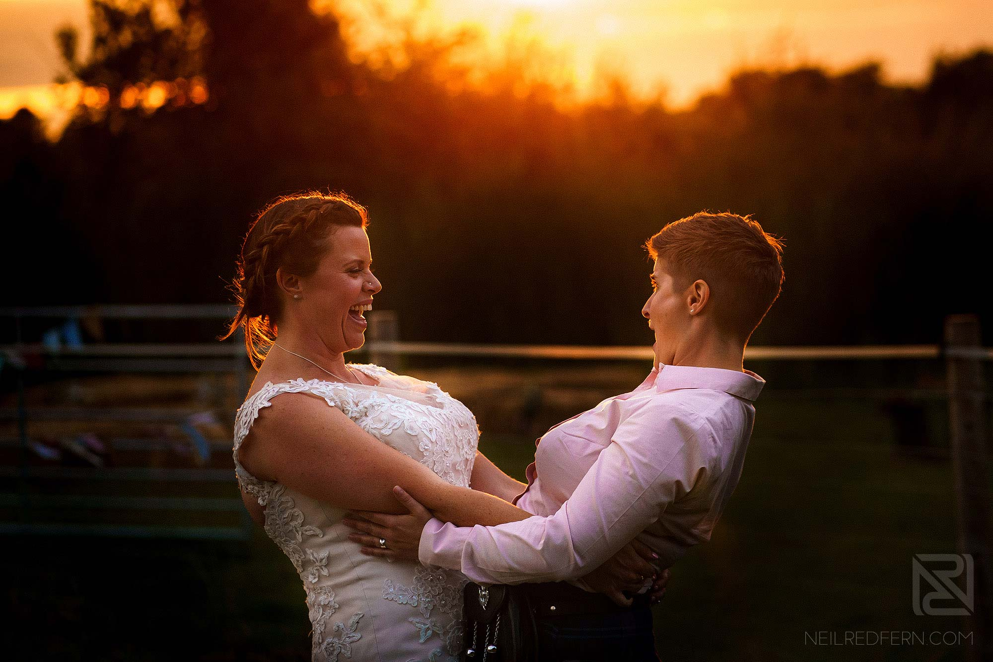 portrait of brides laughing at sunset