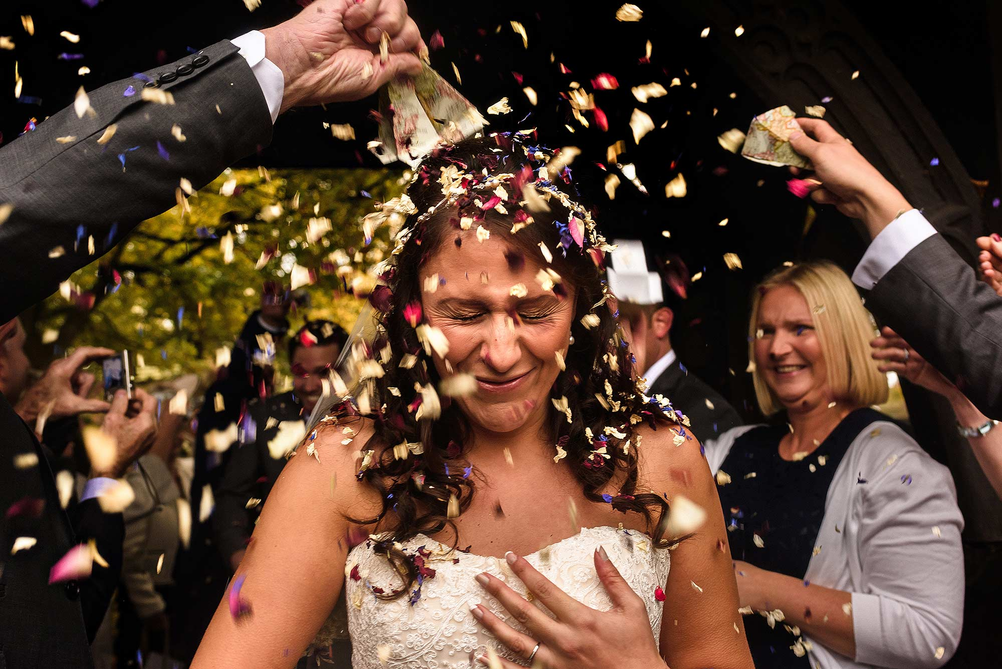 unposed moment of bride having confetti poured on her