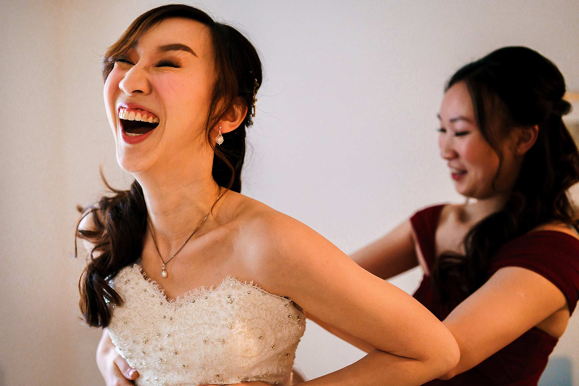 unposed photograph of bride laughing as she puts on wedding dress