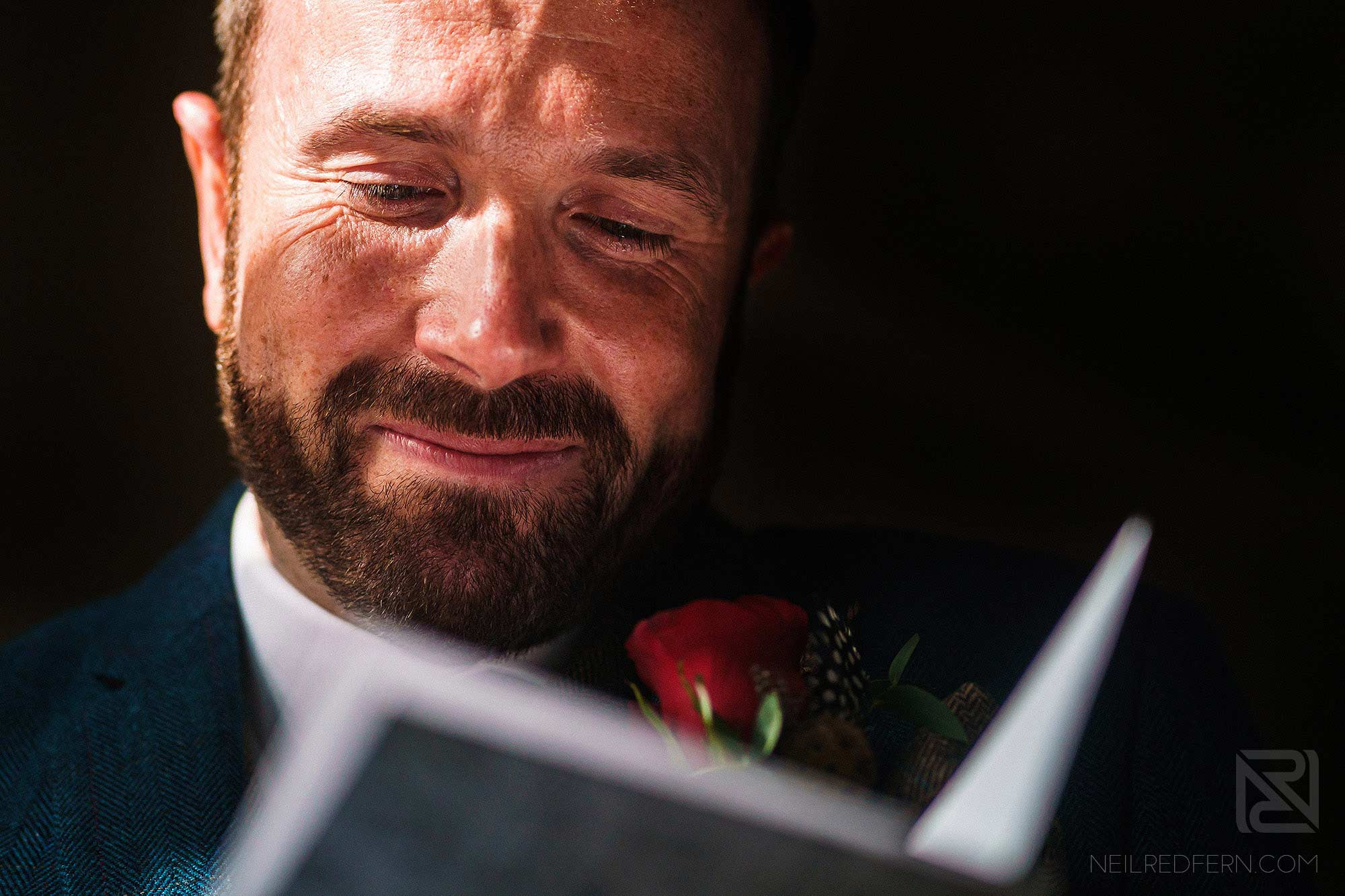 groom crying whilst ready a card