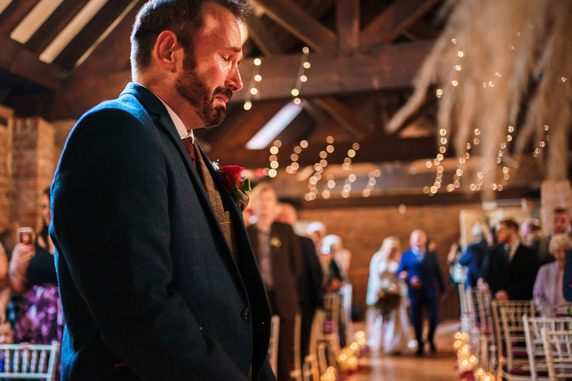 emotional groom waiting for bride to walk down the aisle