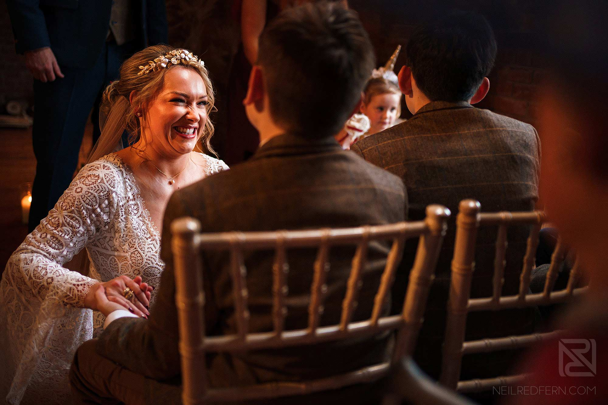 bride smiling at page boy during wedding ceremony